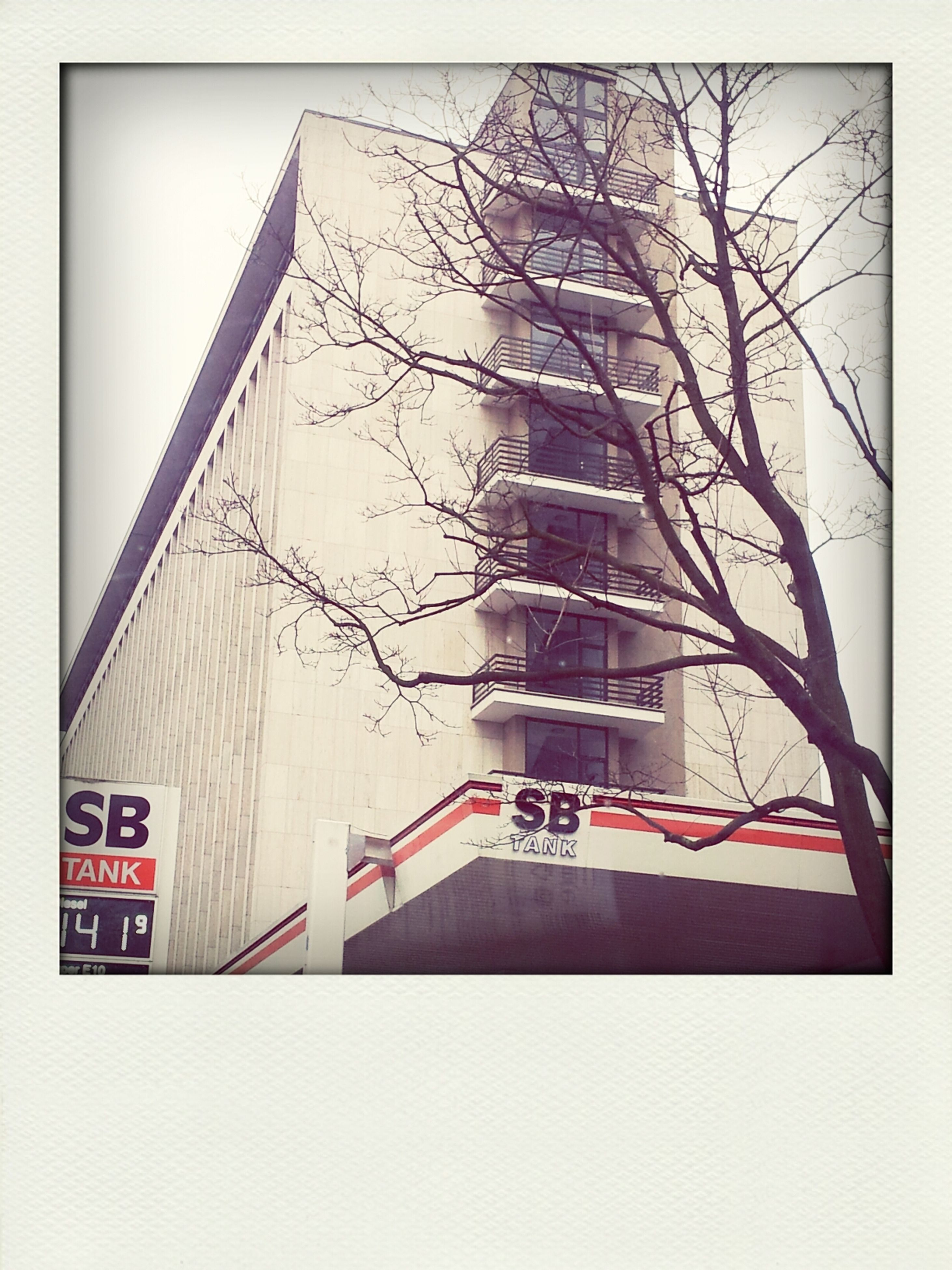 architecture, building exterior, built structure, low angle view, transfer print, auto post production filter, bare tree, building, city, tower, no people, day, sky, outdoors, clear sky, text, tall - high, tree, communication, residential building