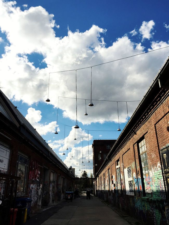 """Lamps outdoors against a blue sky with fluffy clouds in front of """"Treptower Hallenflohmarkt"""" in Berlin Architecture Berlin Building Built Structure Cable City Cloud Cloud - Sky Cloudy Day Diminishing Perspective Empty Lamps No People Outdoors Power Line  Residential Building Residential District Residential Structure Sky The Way Forward Town Treptower Park Vanishing Point Weather"""
