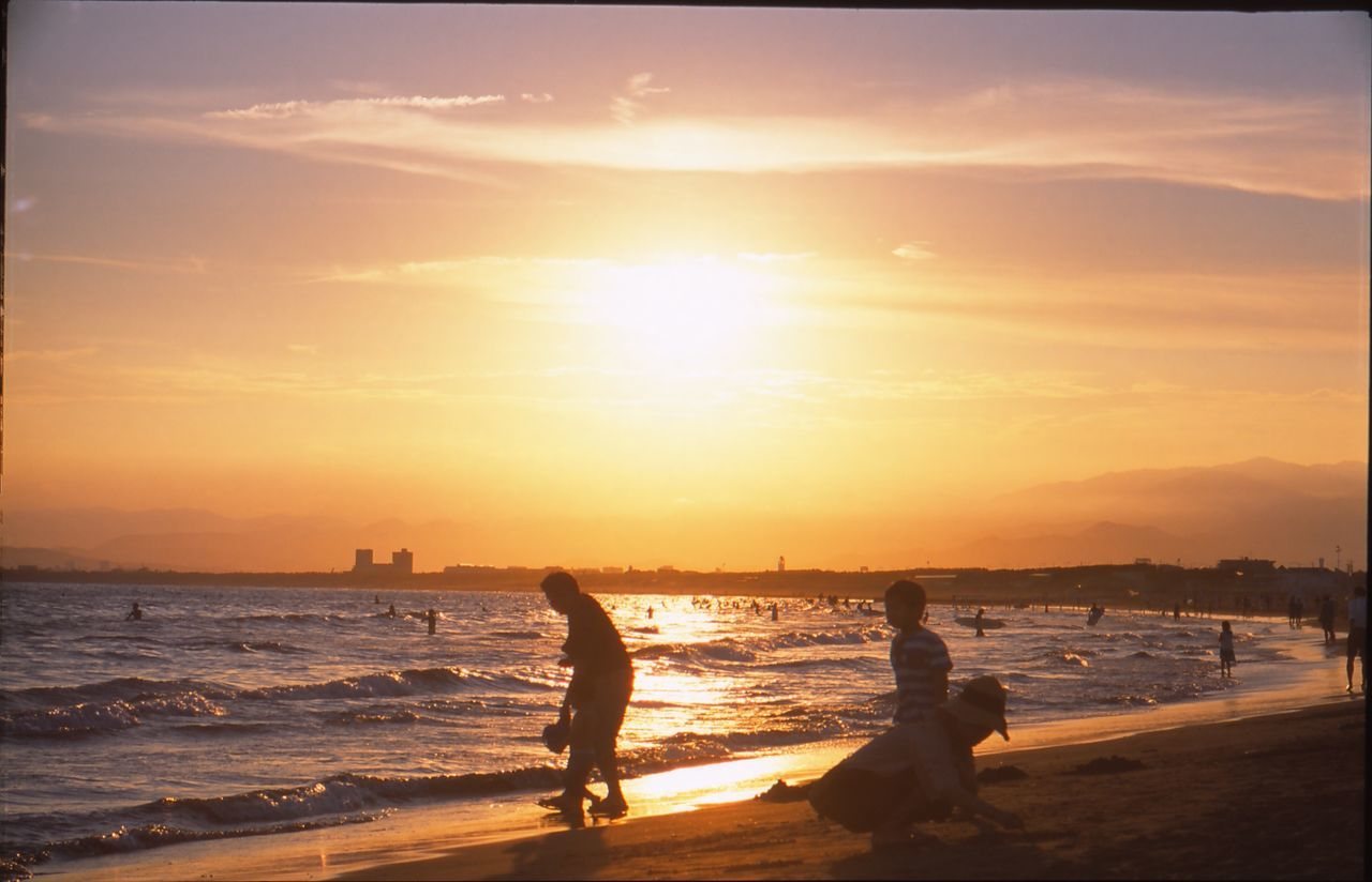 sunset, sea, beach, water, sunlight, sky, silhouette, orange color, sun, leisure activity, real people, beauty in nature, nature, sand, scenics, outdoors, enjoyment, lifestyles, togetherness, vacations, men, wave, horizon over water, friendship, day, people