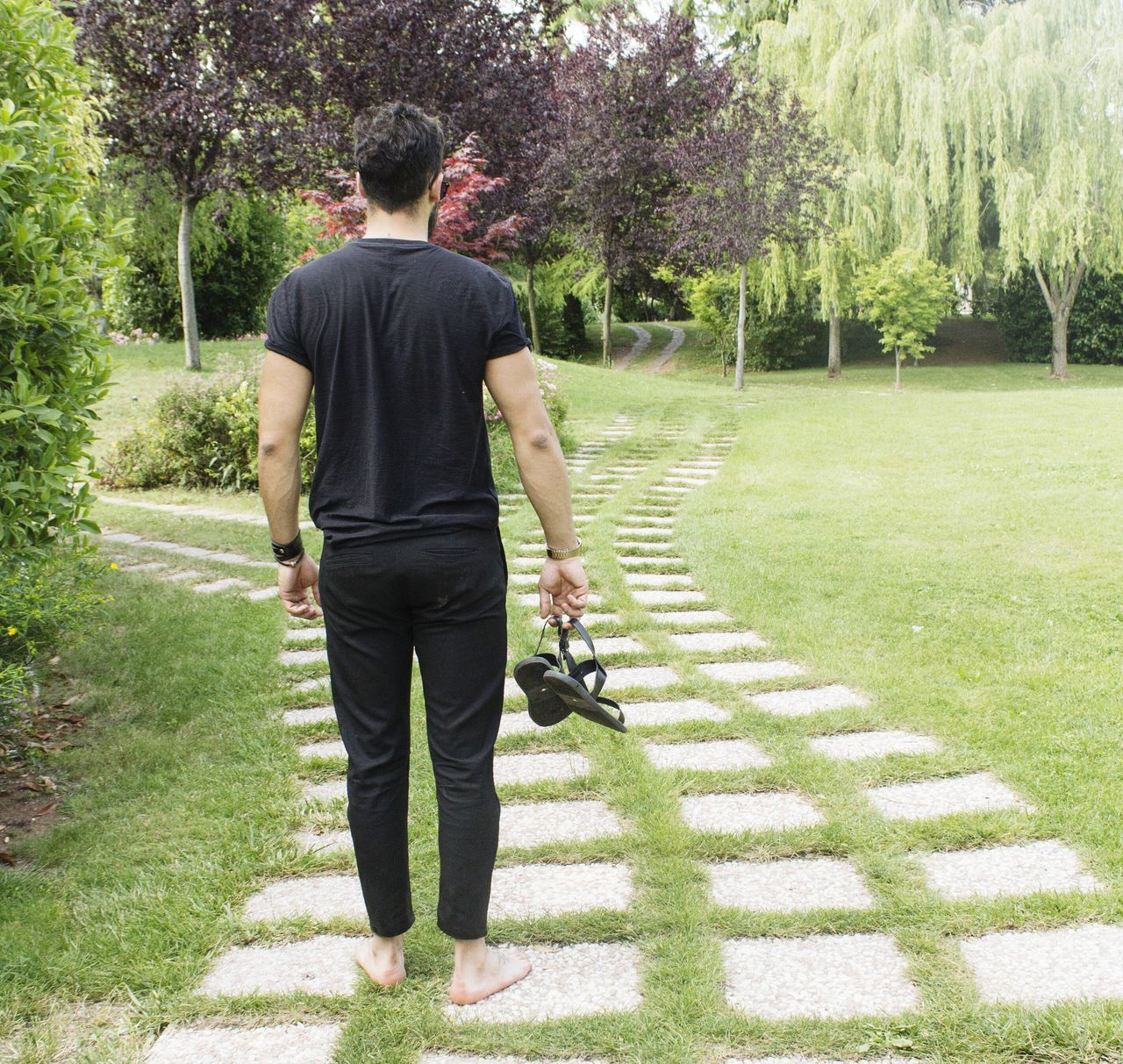 rear view, tree, walking, grass, full length, casual clothing, one person, the way forward, park - man made space, day, real people, men, outdoors, growth, nature, young adult, one man only, only men, adult, people, adults only