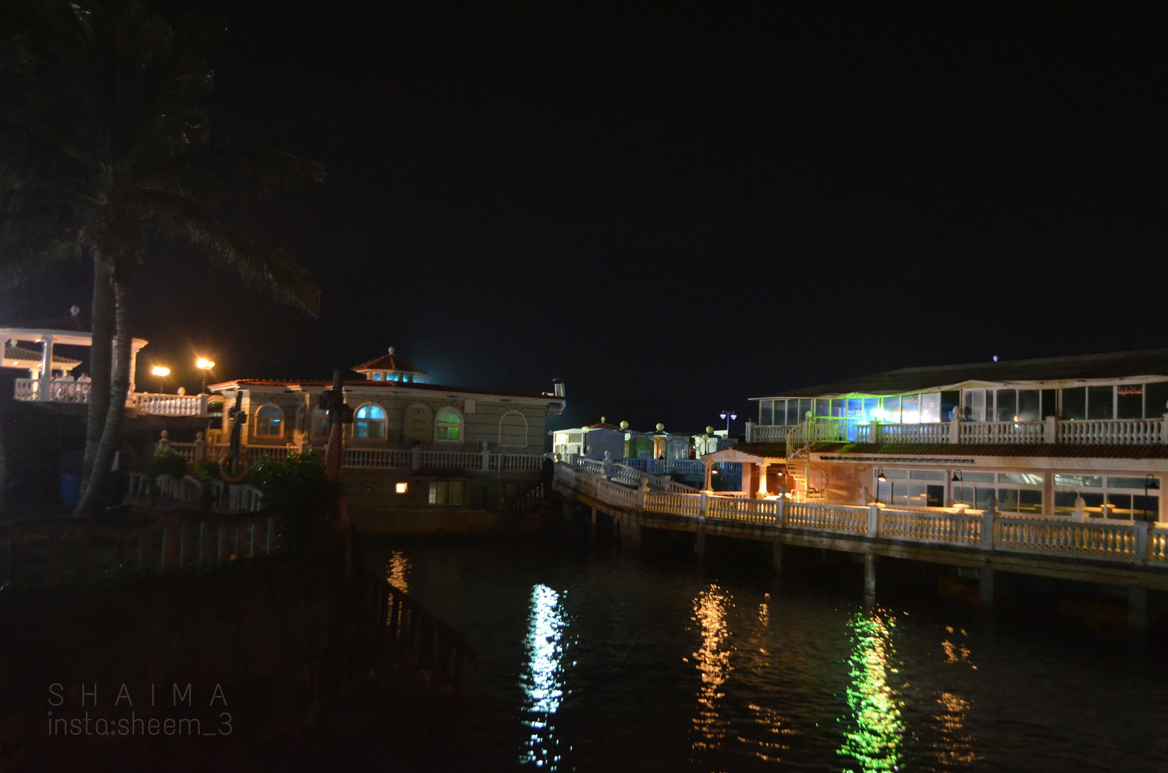 water, night, building exterior, illuminated, built structure, architecture, reflection, waterfront, river, canal, clear sky, transportation, city, copy space, outdoors, street light, mode of transport, no people, house, sky