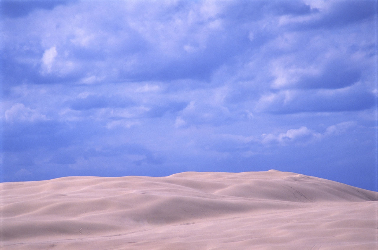 Scenic View Of Desert Against Cloudy Sky