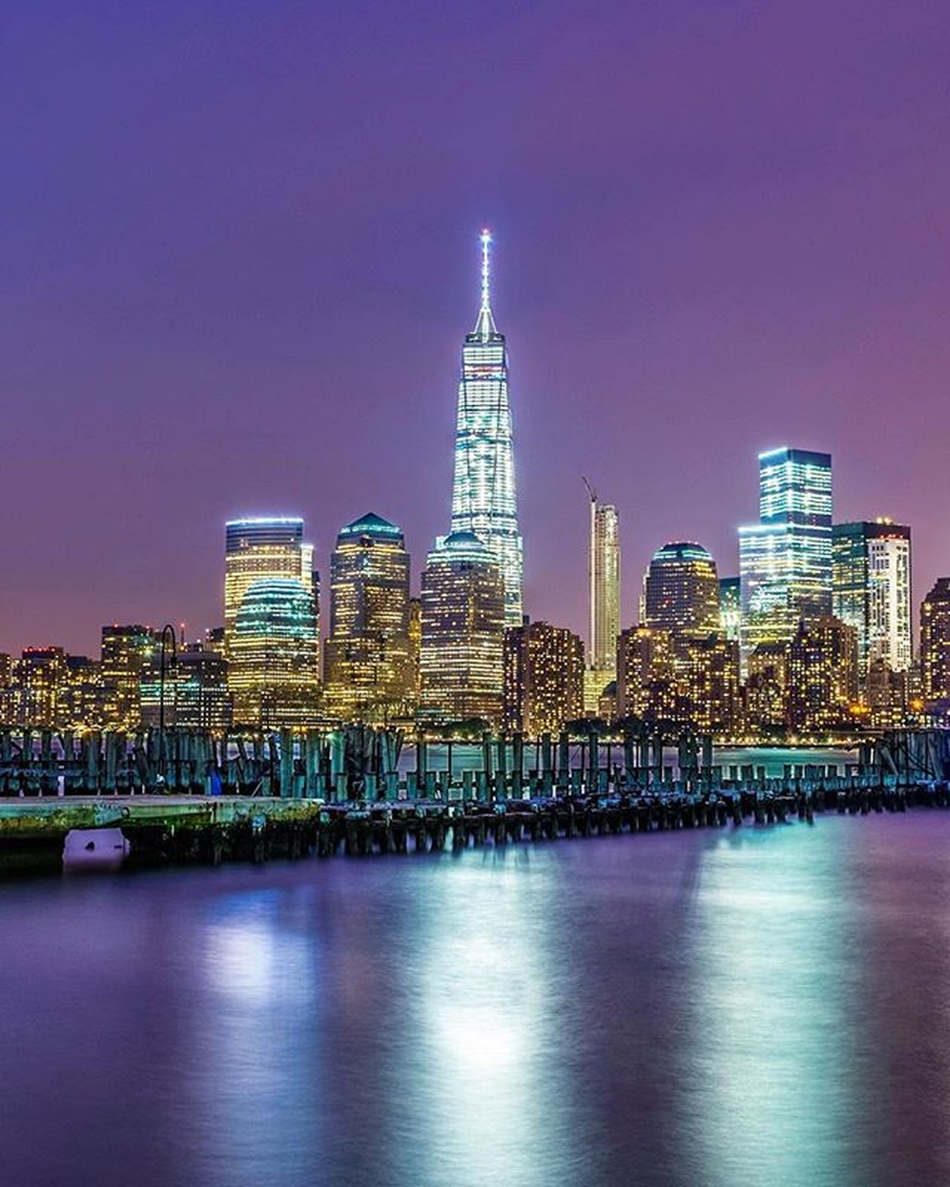 architecture, illuminated, building exterior, built structure, city, skyscraper, night, cityscape, modern, tall - high, tower, urban skyline, office building, waterfront, clear sky, water, financial district, capital cities, river, reflection