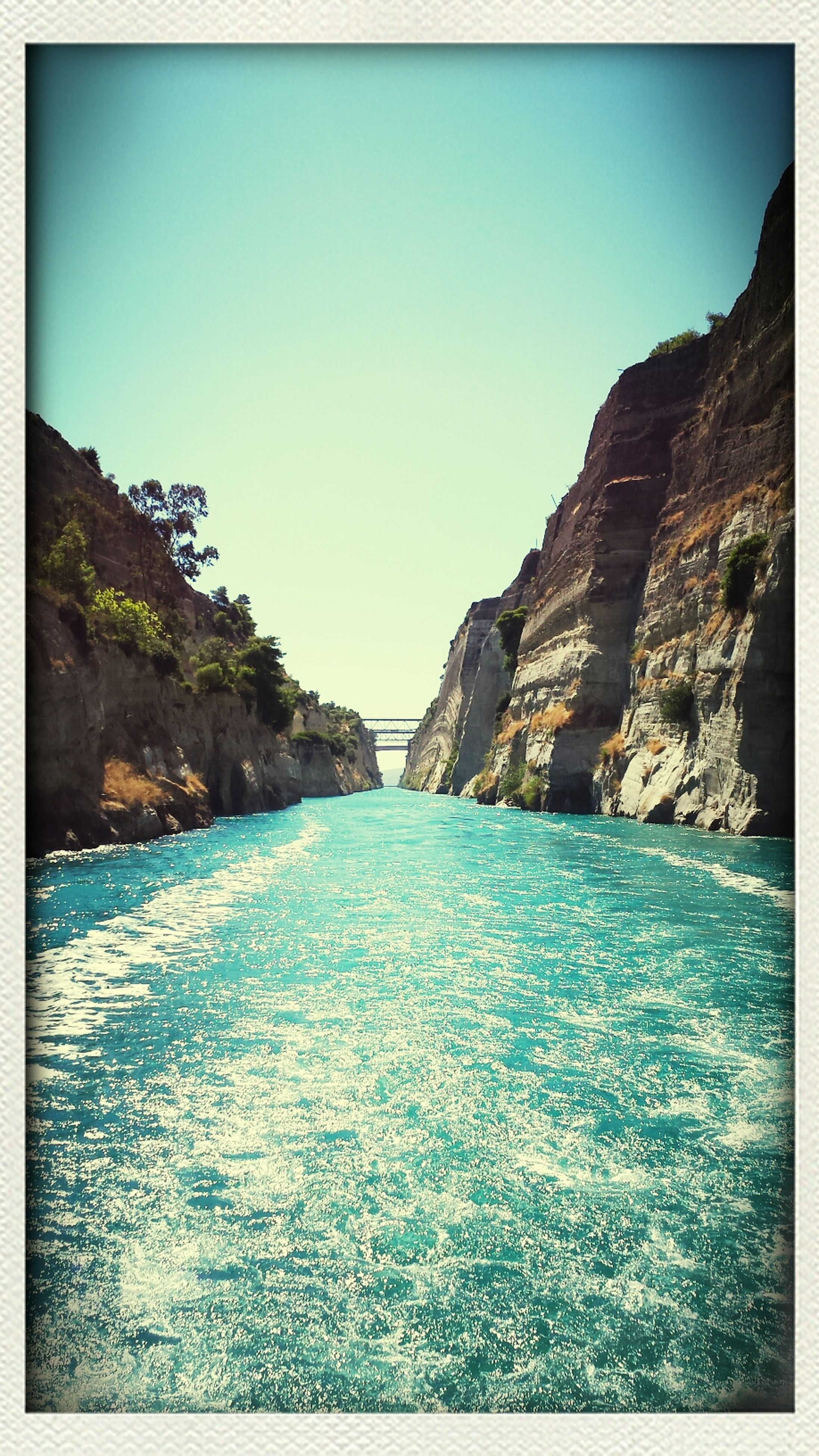 transfer print, water, clear sky, sea, auto post production filter, scenics, tranquil scene, blue, tranquility, beauty in nature, rock formation, nature, rock - object, copy space, mountain, rock, waterfront, beach, cliff, idyllic