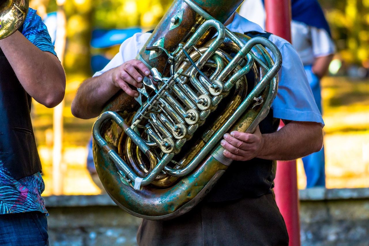 Close-up Concert Cropped Day Detail Focus On Foreground Fun Group Leisure Activity Lifestyles Live Music Man Musical Instrument Musical Instruments Musician Outdoors Part Of Playing Skill  Sunny Traditional Music Tuba