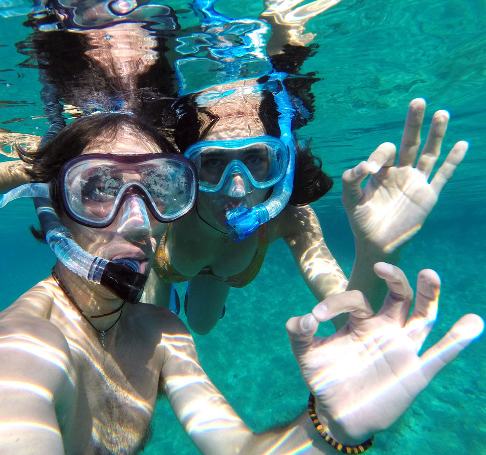 Underwater view of a couple snorkeling in the sea Blue Clear Water Couple Diving Exploring Floating Leisure Activity Man Ocean Ok Sign People Sea Snorkeling Snorkeling Snorkeling Mask Summer Swimming Swimming Swimming Pool Underwater Underwater Diving Vacation Water Water Woman