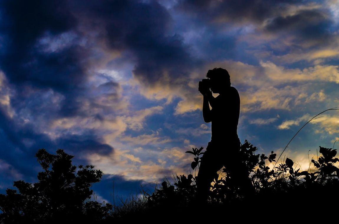 Silhouette Cloud - Sky Sky Photographing Photography Themes Technology Low Angle View Outdoors Camera - Photographic Equipment Wireless Technology Sunset (null)Communication Nature Real People Beauty In Nature Men Mobile Phone Leisure Activity One Person Standing