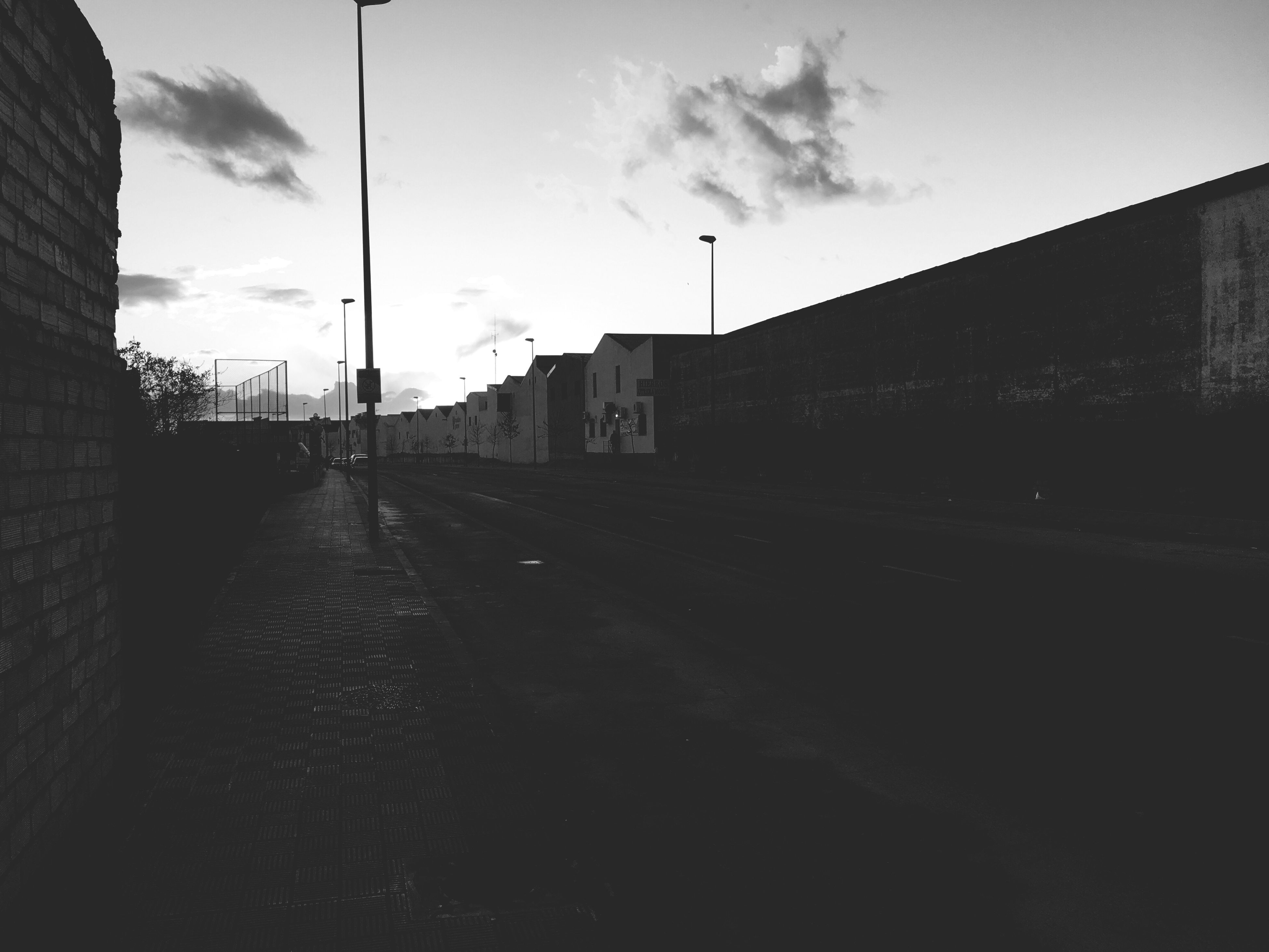 sky, architecture, built structure, road, street, building exterior, empty, cloud - sky, the way forward, house, cloud, empty road, long, day, cloudy, outdoors, surface level, diminishing perspective, no people