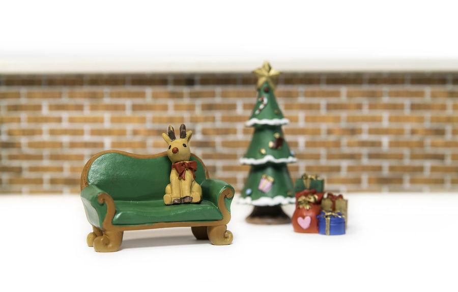 Reindeer sitting on long green bench near Christmas tree Brick Wall Christmas Reindeer Sighting Animal Representation Childhood Christmas Tree Day Figurine  Green Color Indoors  No People Toy