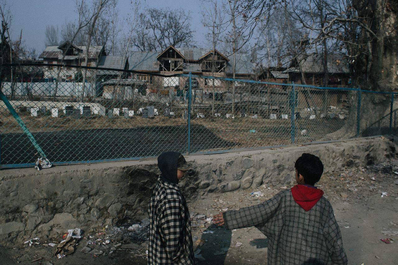 Two kids walking by the Martyr graveyard of Palhalan, Kashmir. 2016