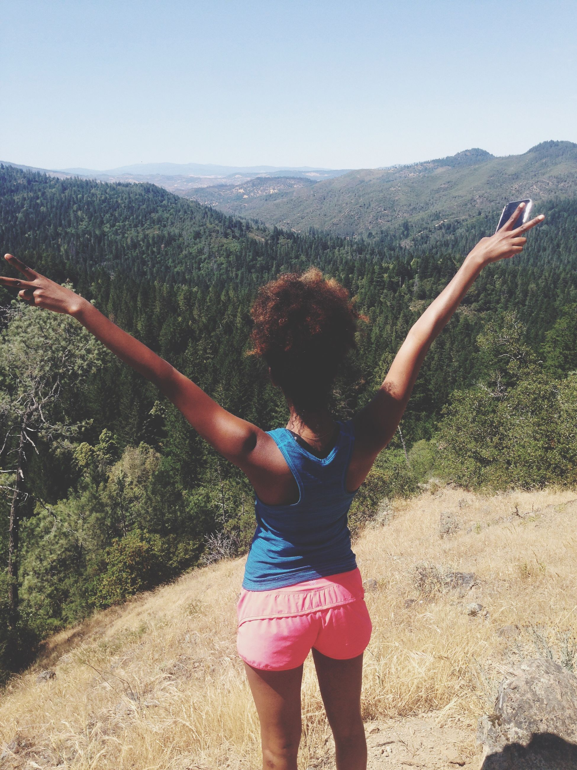 lifestyles, casual clothing, leisure activity, full length, standing, clear sky, rear view, mountain, three quarter length, young adult, nature, tranquil scene, sky, beauty in nature, tree, person, tranquility, young women