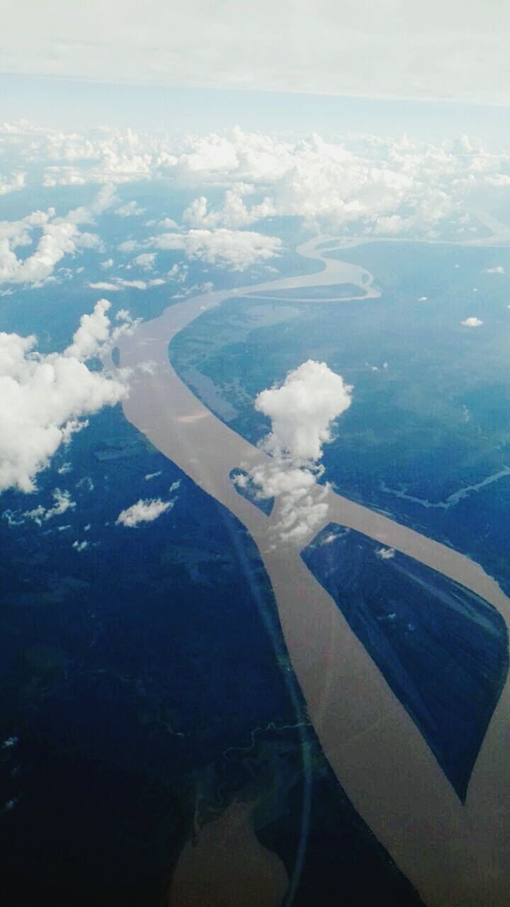 aerial view, agriculture, cloud - sky, scenics, day, beauty in nature, airplane, mid-air, sea, patchwork landscape, outdoors, landscape, nature, rural scene, flying, no people, water, sky, view into land