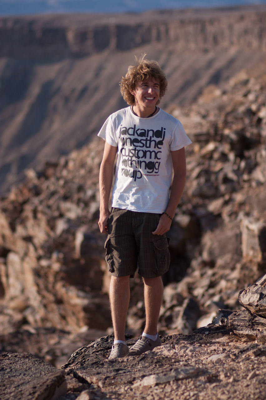 Full Length of Young Man Looking Away While Standing On Rocks In Desert