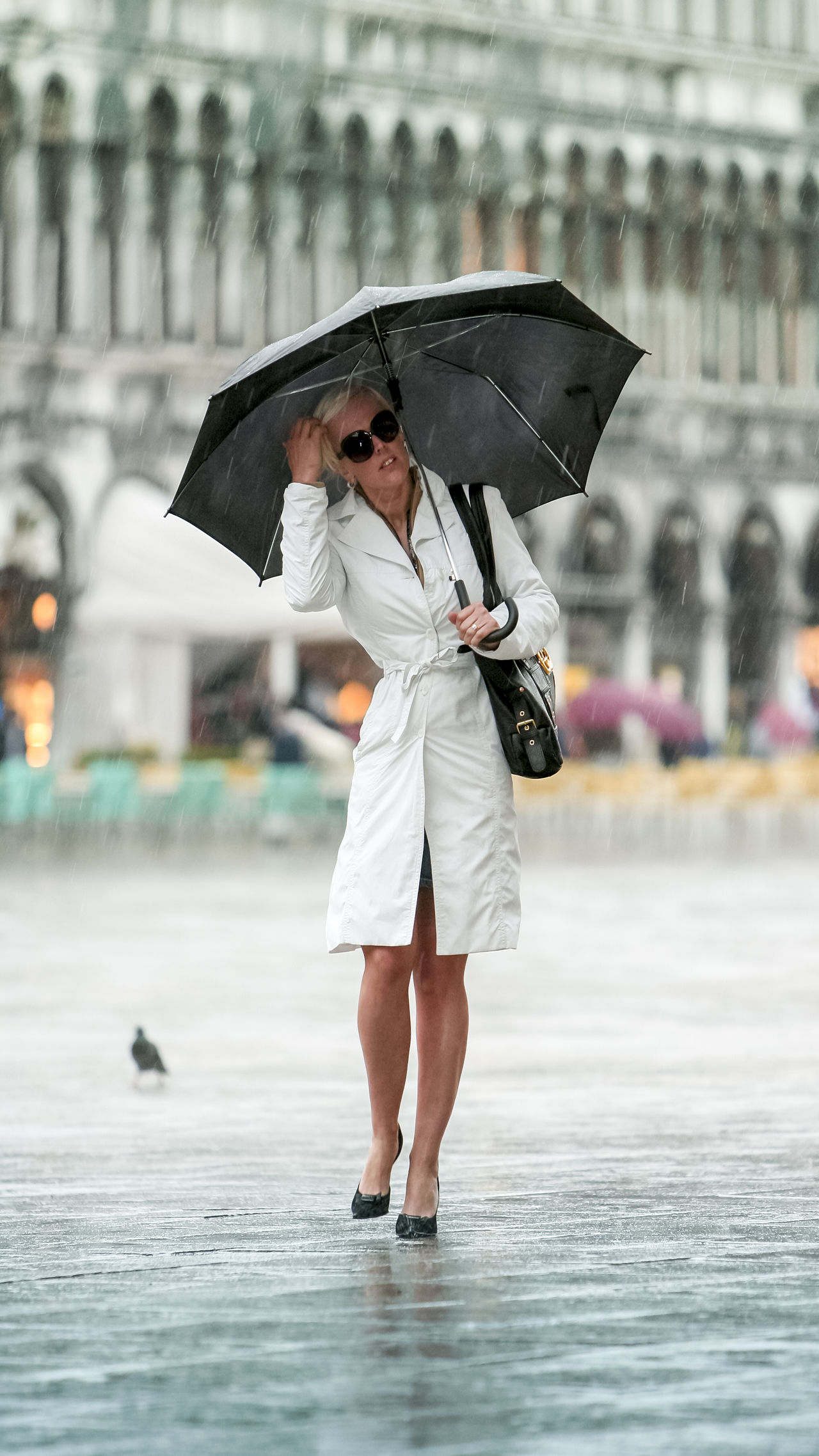 elegant dressed girl walks alone in the peak tourist season the center of St. Mark's Square Venice under the umbrella of rain In The Peak Tourist Season Adult Center Of St. Mark's Square Venice Day Dressed Elegant Girl Walks Alone One Person One Woman Only Outdoors People Person Rain Rain Smiling Umbrella Vertical Water