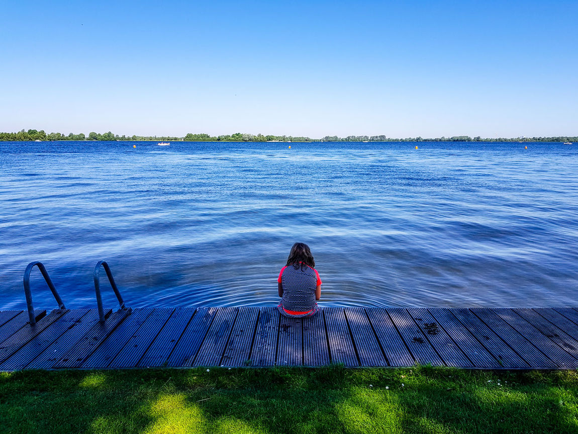 Horizon Over Water Beauty In Nature Nature Day Clear Sky Sky One Young Woman Only Outdoors Sitting One Person Water Blue Rear View Lonliness Waiting Waiting For Daddy Samsungphotography Netherlands SamsungS8Plus Mobilephotography GalaxyS8+ Galaxy S8+ Sunny Day River Live For The Story BYOPaper! The Great Outdoors - 2017 EyeEm Awards Place Of Heart