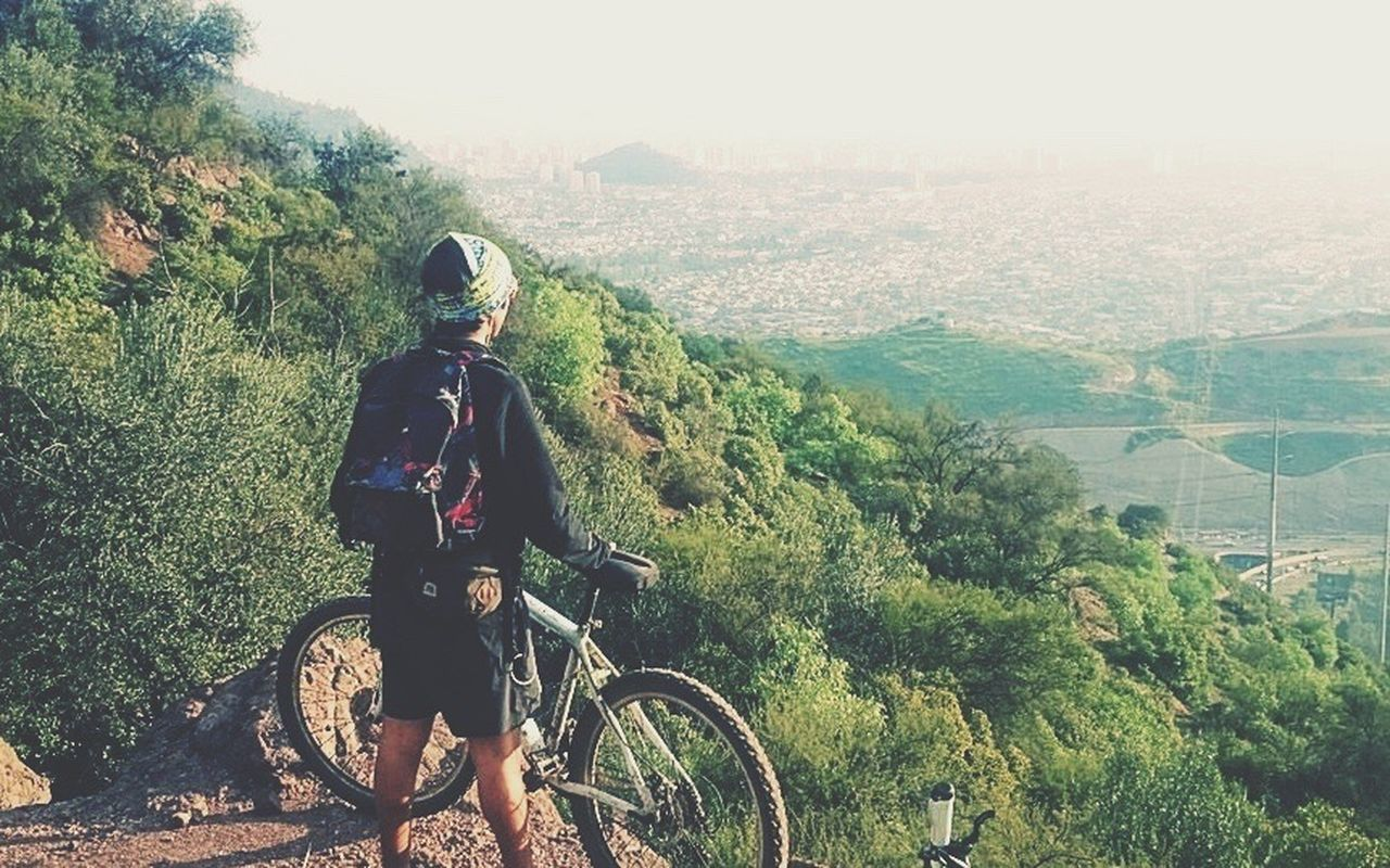bicycle, transportation, real people, cycling, one person, mode of transport, backpack, day, riding, helmet, nature, tree, mountain, adventure, land vehicle, cycling helmet, lifestyles, outdoors, sports helmet, mountain bike, landscape, full length, scenics, beauty in nature, headwear, sky, people