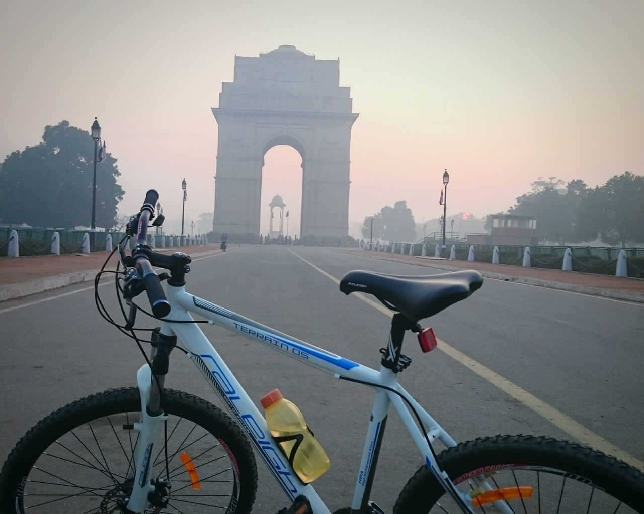 bicycle, transportation, mode of transport, architecture, land vehicle, built structure, travel, travel destinations, sunset, outdoors, triumphal arch, city, building exterior, day, sky, no people
