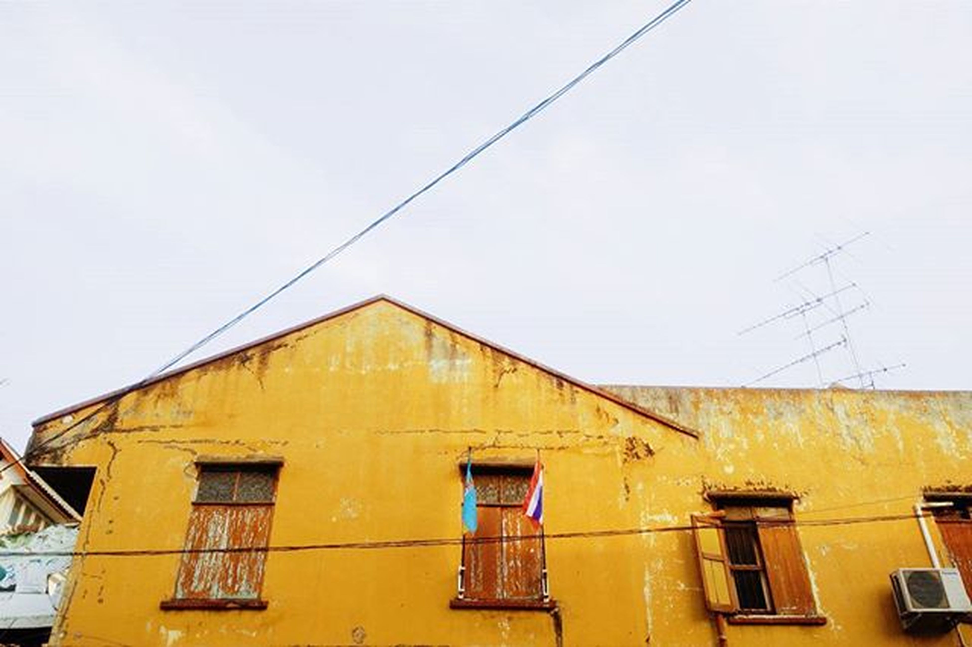 architecture, building exterior, built structure, low angle view, residential structure, residential building, house, window, power line, building, cable, clear sky, day, outdoors, no people, sky, roof, high section, copy space, yellow