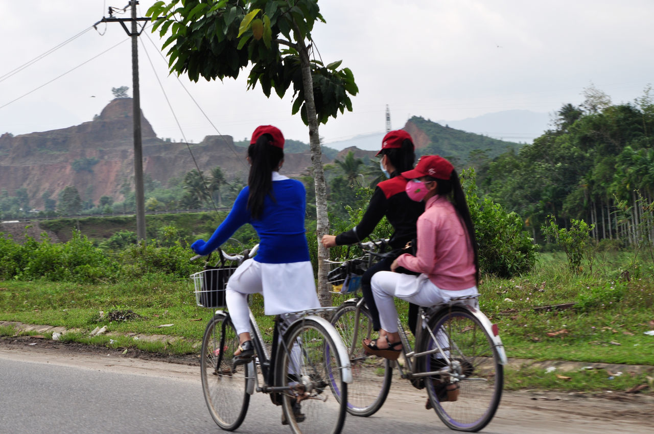 Schoolgirls cycling home along country road near Danang in Vietnam. Ao Dai Bicycles Countryside Cycling Danang Facemasks Friends Going Home Greenery Long Hair Pedalling Ponytails Quarries Roads Rural School Uniform Schoolgirls Trees Vietnam