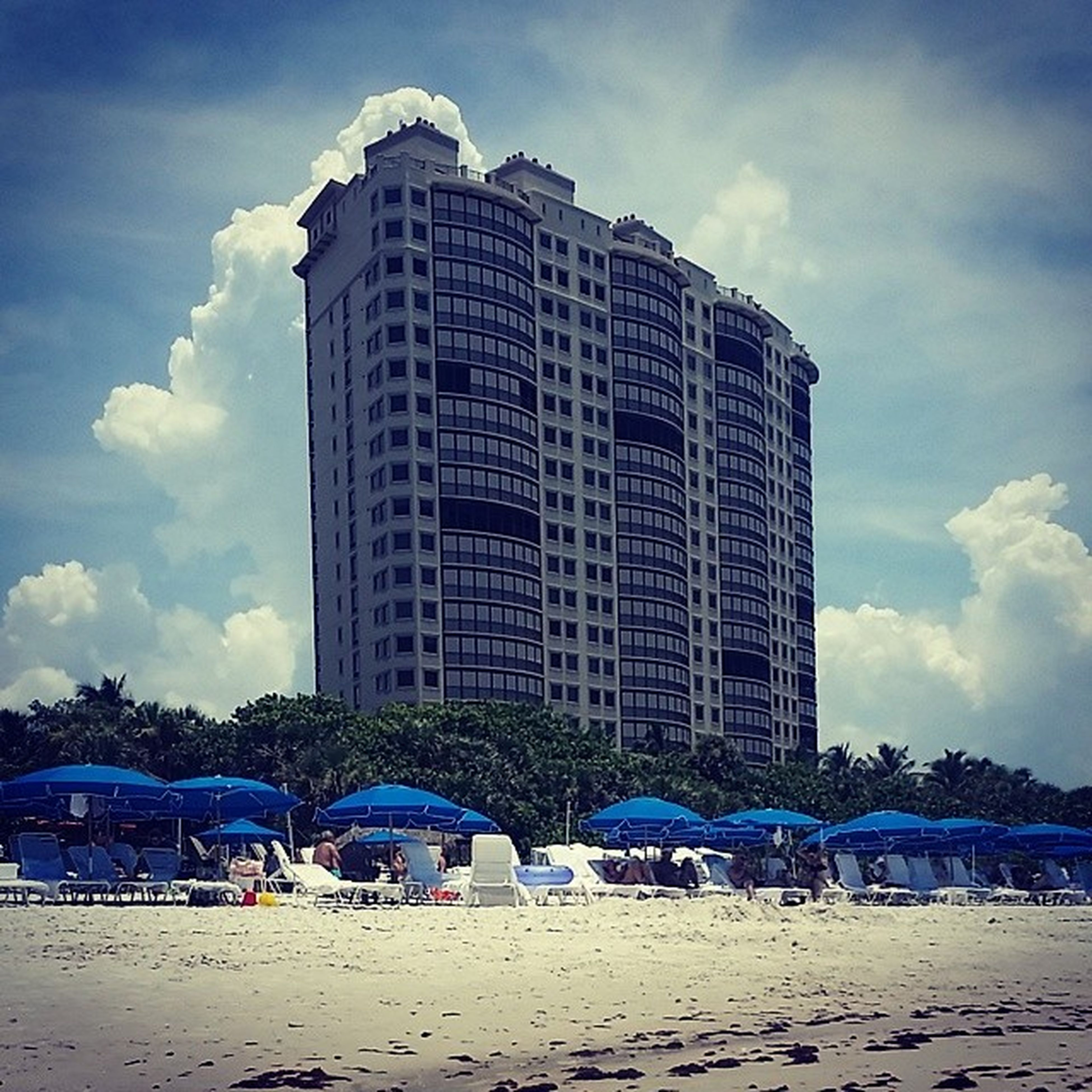 building exterior, beach, architecture, sky, built structure, sand, cloud - sky, shore, city, cloud, sea, day, vacations, chair, water, cloudy, outdoors, sunlight, blue, incidental people