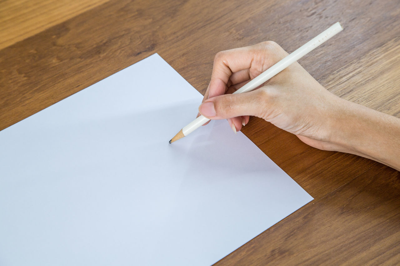 Cropped Image Of Woman Writing On Paper