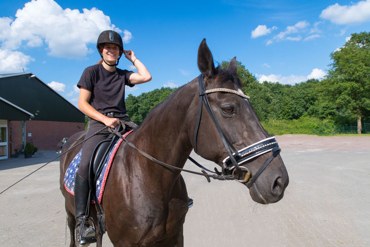 Black Horse Bridle Casual Clothing Cloud Cloud - Sky Domestic Animals Girl Happy Happy Girl  Horse Leisure Activity Lifestyles Livestock Mammal One Animal Outdoors Riding Riding School Sky Teenager Working Animals Young Adult