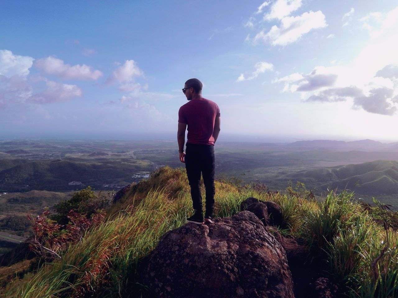 rear view, nature, sky, real people, beauty in nature, scenics, standing, full length, tranquility, one person, tranquil scene, casual clothing, outdoors, rock - object, landscape, leisure activity, cloud - sky, mountain, day, men, lifestyles, people
