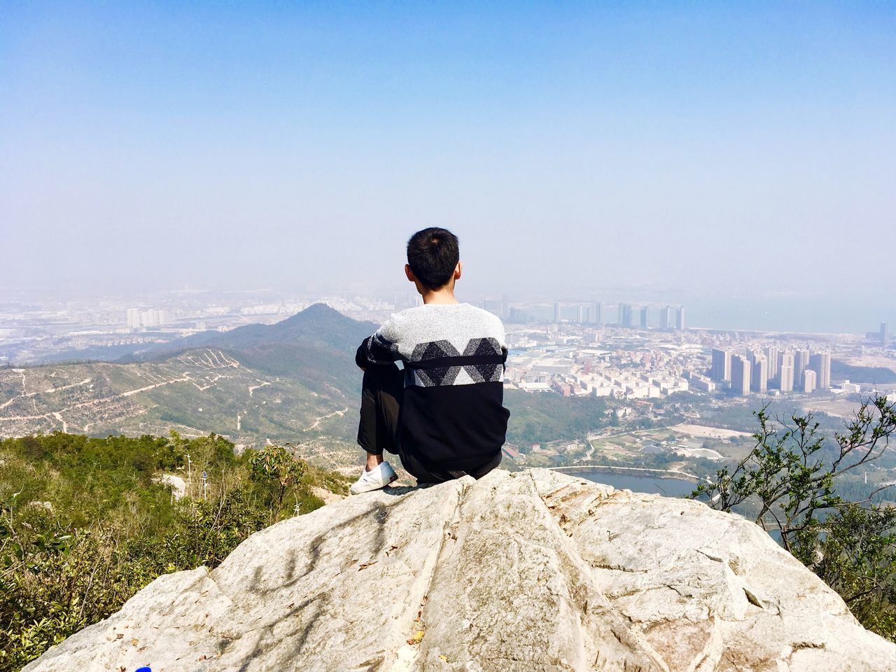 Rear View Of Man Sitting On Rock While Looking At Landscape Against Sky From Mountain Peak