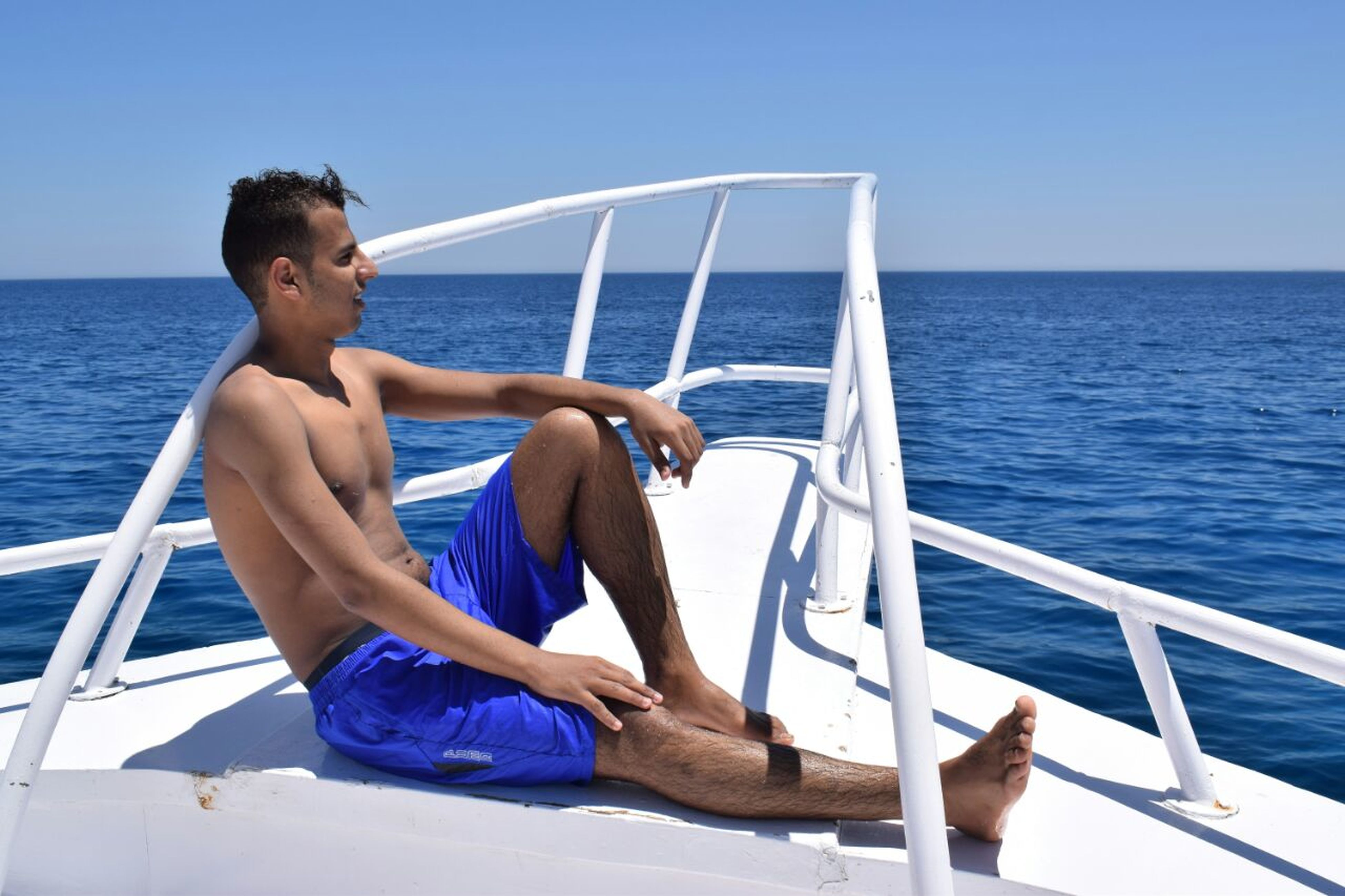 sea, horizon over water, water, nautical vessel, nature, beauty in nature, mode of transport, transportation, sky, leisure activity, sailing, outdoors, summer, one person, lifestyles, full length, men, sunlight, clear sky, scenics, blue, day, young adult, boat deck, real people, people