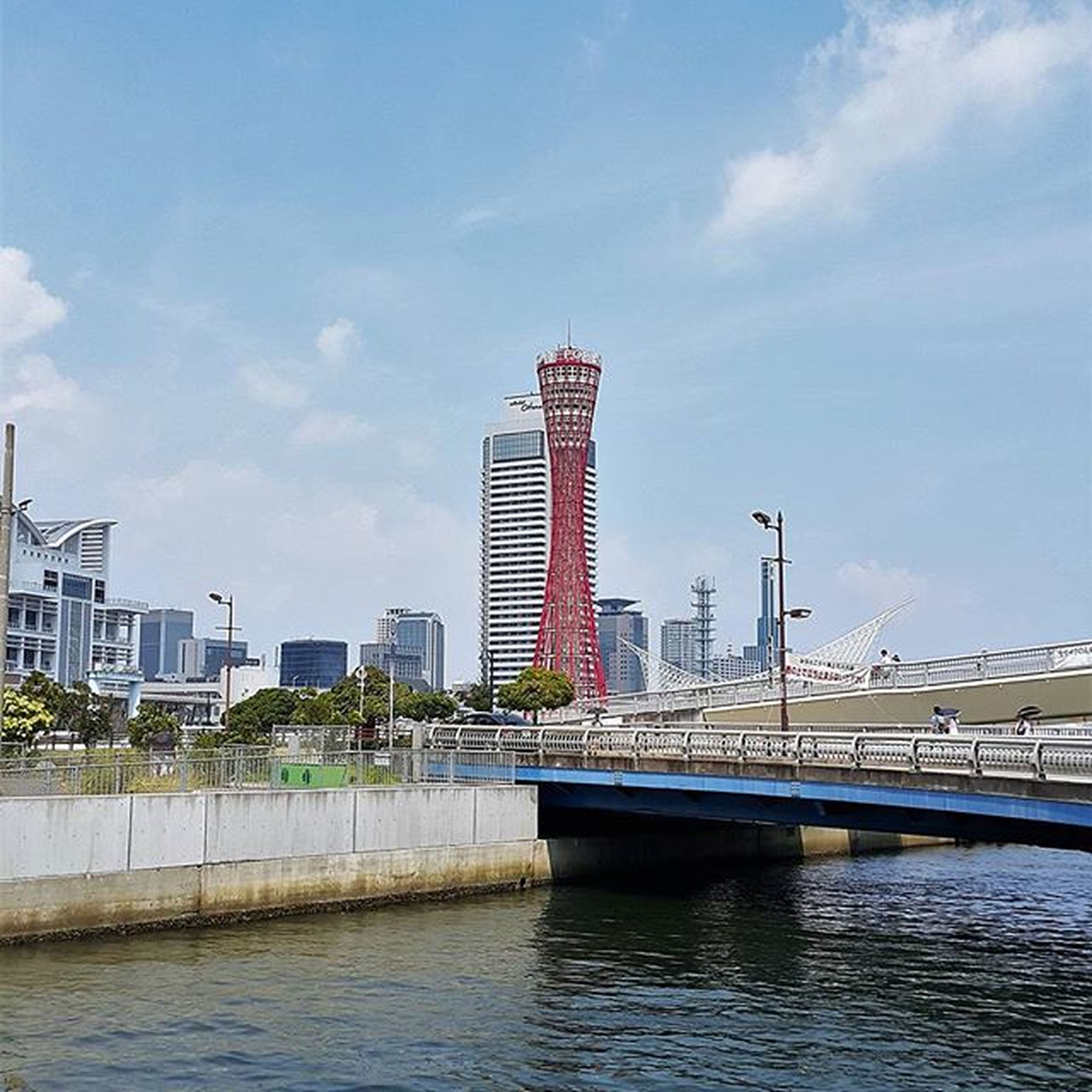 architecture, built structure, building exterior, city, water, sky, waterfront, river, skyscraper, cityscape, modern, urban skyline, office building, connection, cloud, tall - high, cloud - sky, tower, bridge - man made structure, skyline