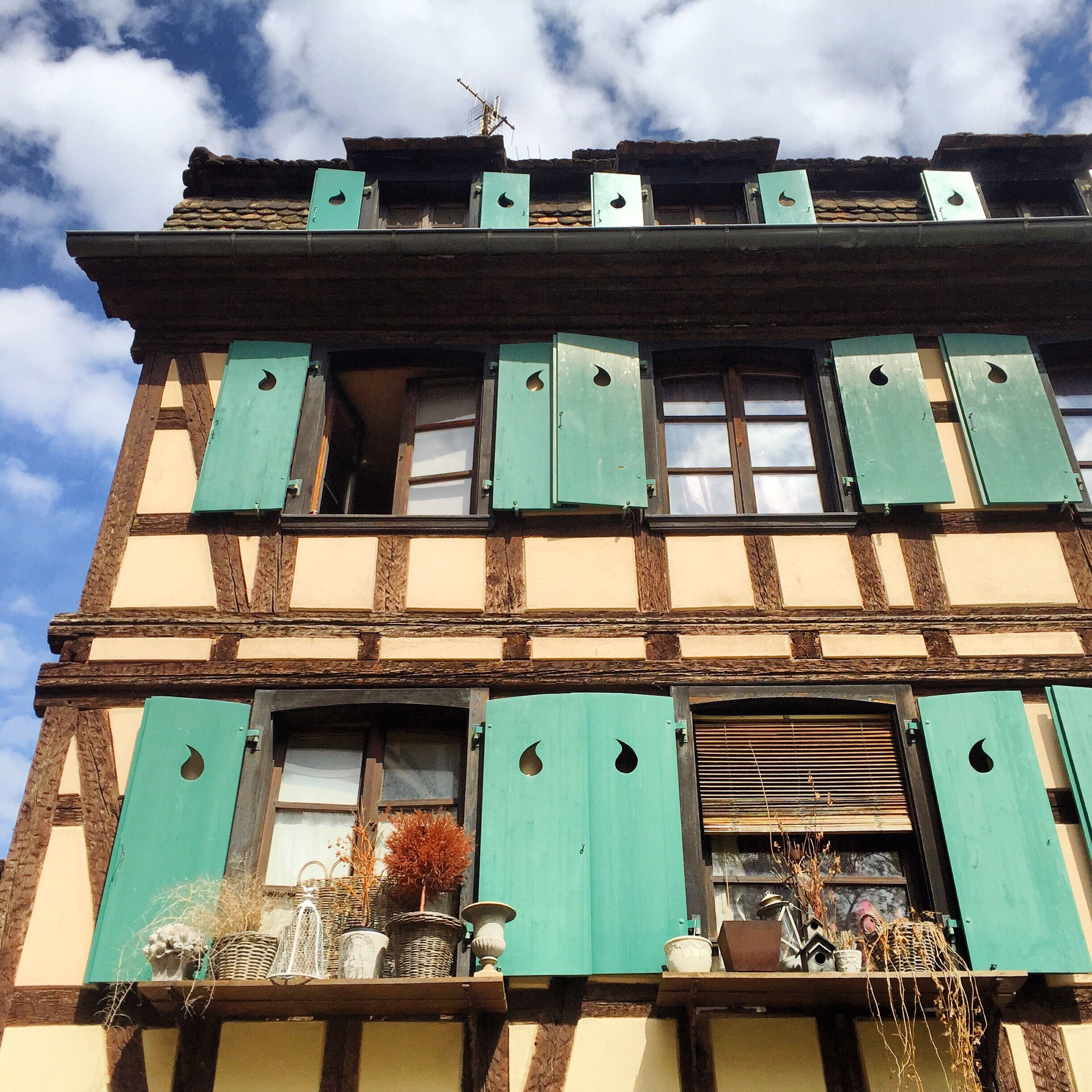 architecture, building exterior, built structure, low angle view, sky, old, window, abandoned, damaged, weathered, blue, residential building, cloud - sky, building, obsolete, run-down, day, residential structure, house, outdoors