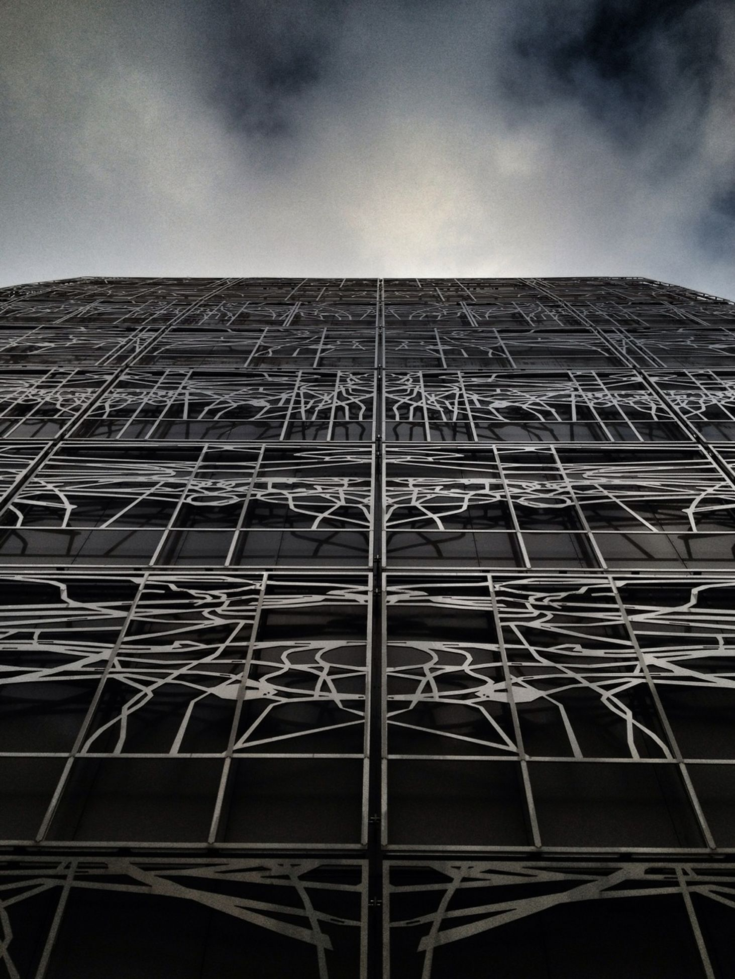 low angle view, architecture, built structure, building exterior, sky, tall - high, modern, tower, cloud - sky, building, office building, glass - material, architectural feature, pattern, day, cloud, tall, no people, outdoors, city