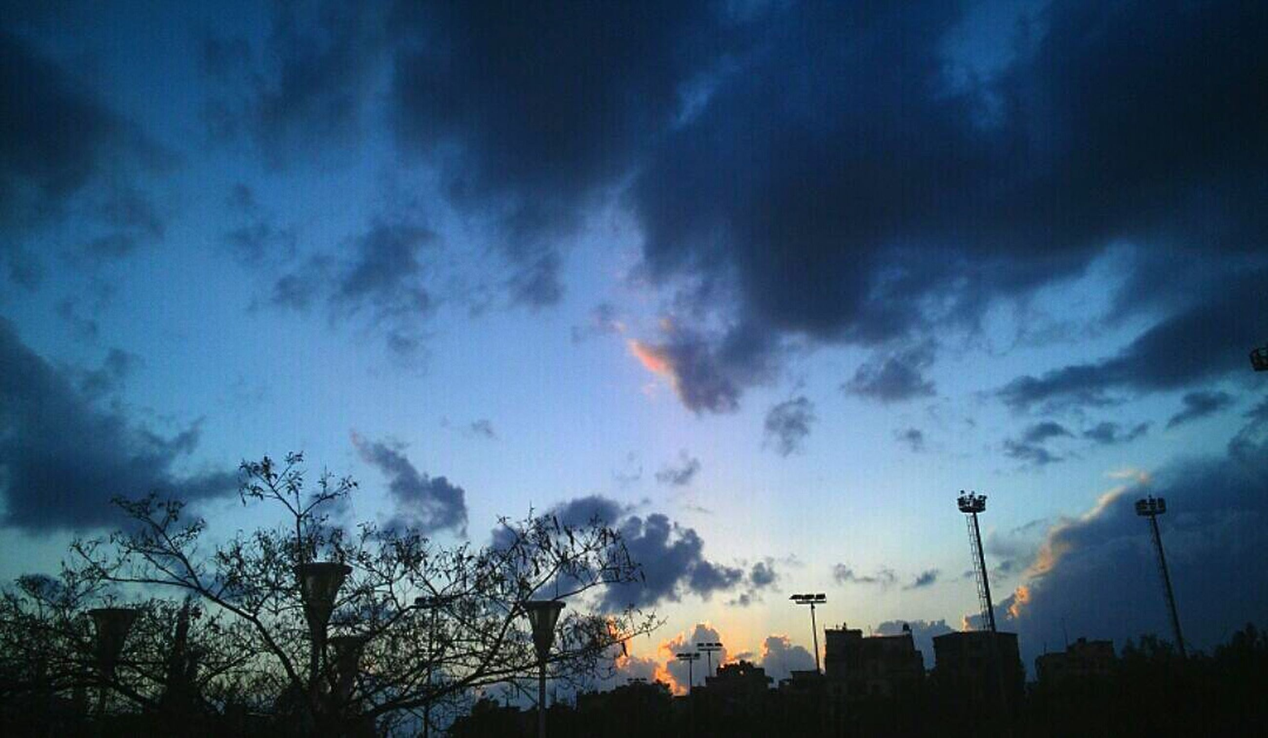 sky, silhouette, low angle view, cloud - sky, cloudy, tree, beauty in nature, sunset, scenics, nature, cloud, dramatic sky, dusk, tranquility, blue, weather, building exterior, overcast, atmospheric mood, tranquil scene