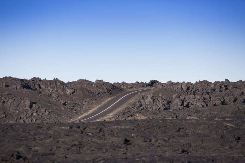 Road through Lava field at hawaiian island Clear Sky Lava Flow Road Arid Climate Beauty In Nature Blue Clear Sky Cold Lava Day Desert Highway Landscape Mountain Nature No People Outdoors Road Scenics Sky Tranquil Scene Transportation Volcanic Landscape Volcano Winding Road