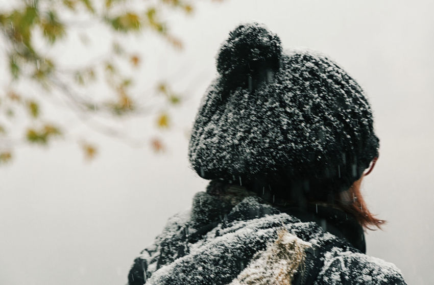 First Snow Adult Branches Bundled Up Cold Temperature Day Freezing Cold Hat Icy Outdoors People Rear View Snow Snowfall Snowing Tree Leaves Twigs And Branches Woman Portrait Wool Wool Hat