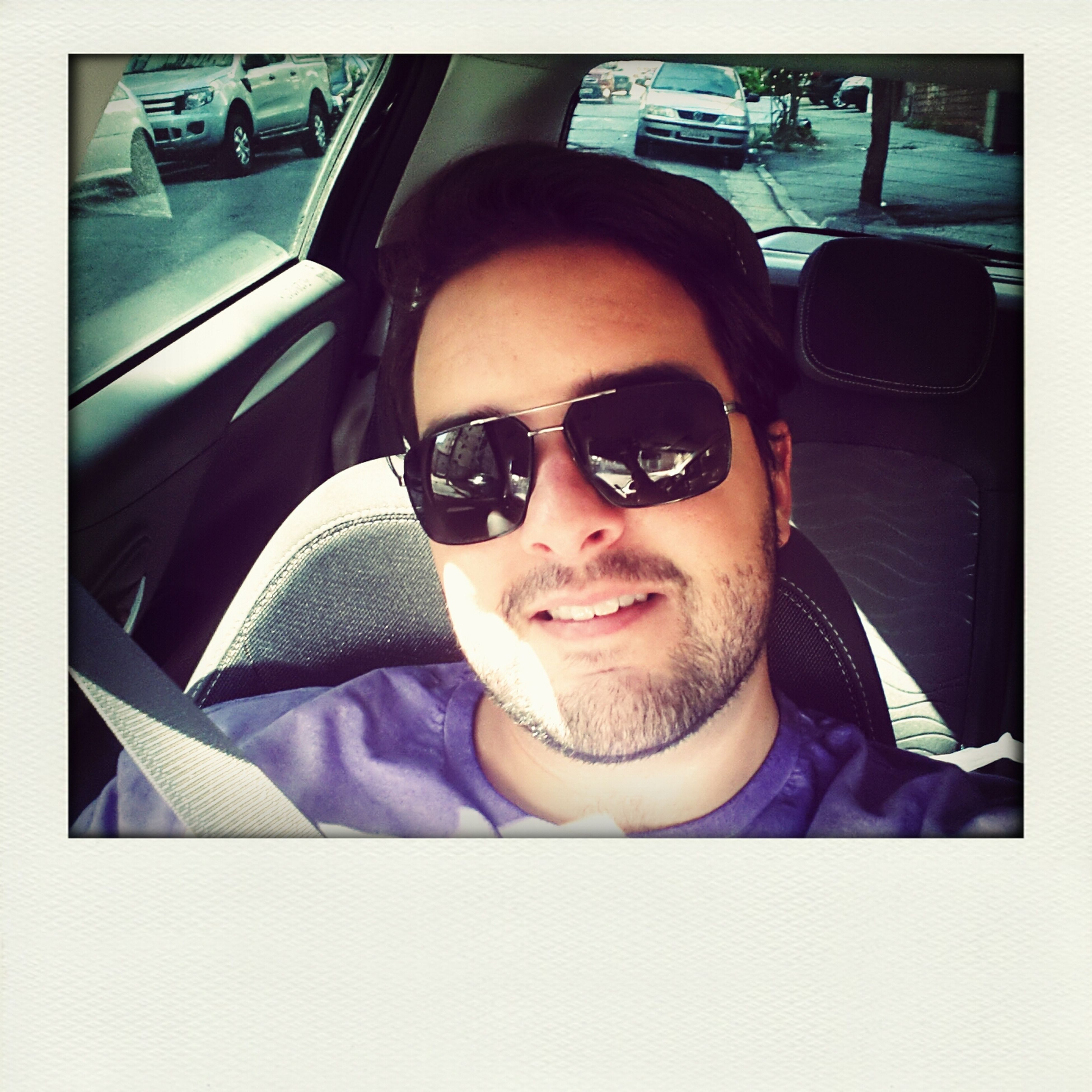 transfer print, looking at camera, car, portrait, transportation, land vehicle, indoors, mode of transport, young adult, person, lifestyles, auto post production filter, front view, sunglasses, leisure activity, sitting, vehicle interior, headshot