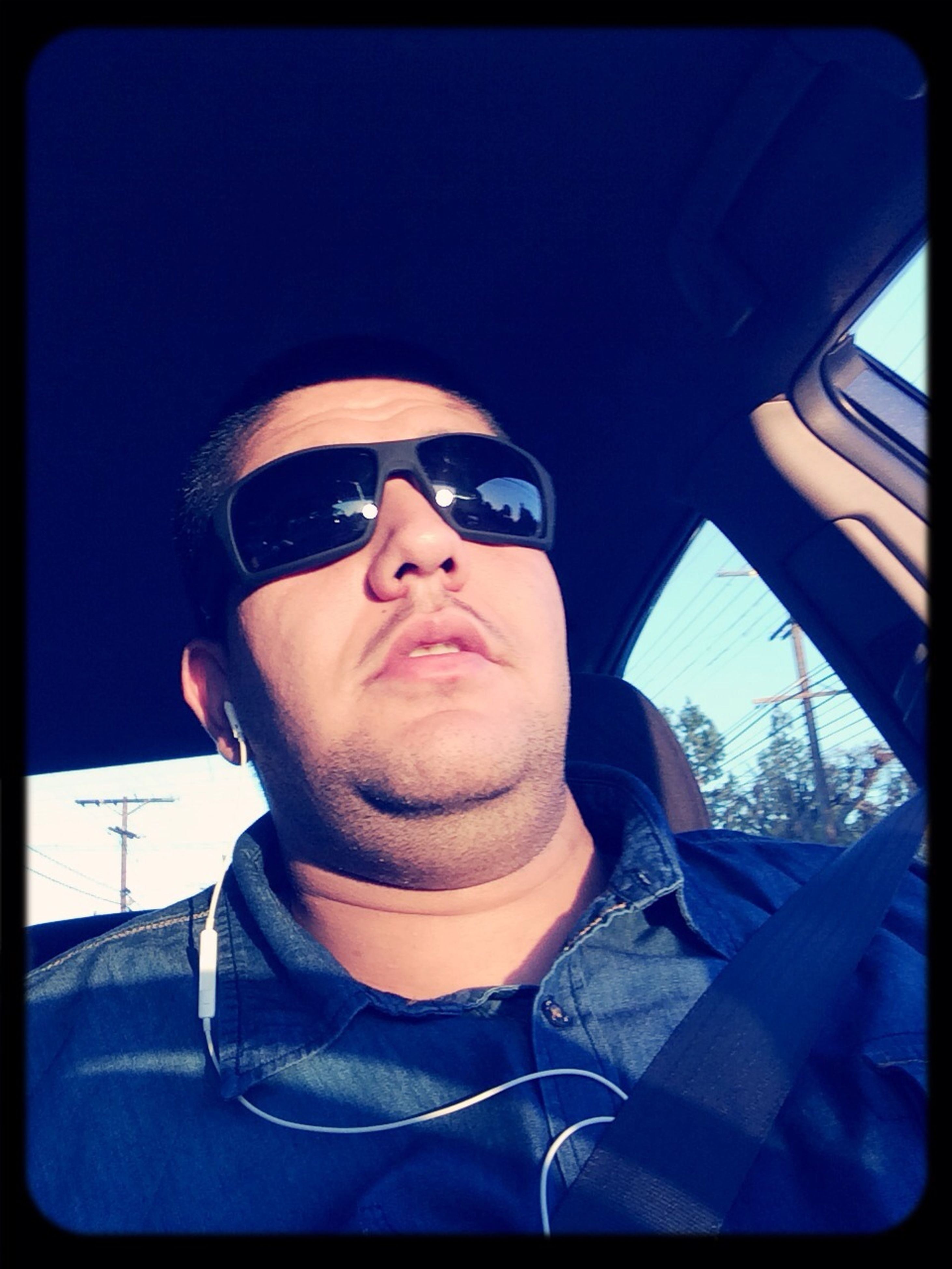 transfer print, looking at camera, portrait, young adult, transportation, auto post production filter, young men, front view, lifestyles, person, sunglasses, mode of transport, leisure activity, car, headshot, vehicle interior, close-up, clear sky