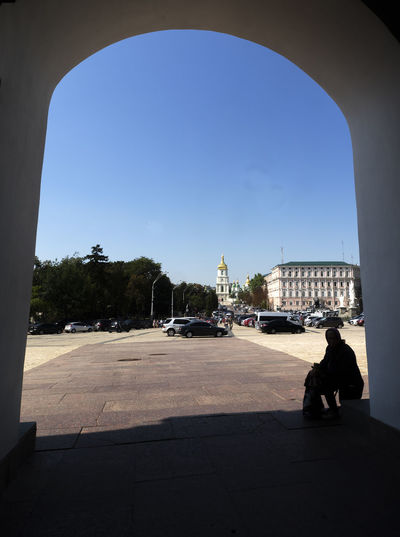 View of Mikhailovskaya and Sofievskaya Square through the arch of the gate of St Mikhayil's Monastery of the Golden Domes Mikhailovskaya Sofievskaya Square View Arch Architecture Building Exterior Built Structure City Day Full Length One Person Outdoors People Shadow Sky Sunlight Transportation Travel Destinations Tree