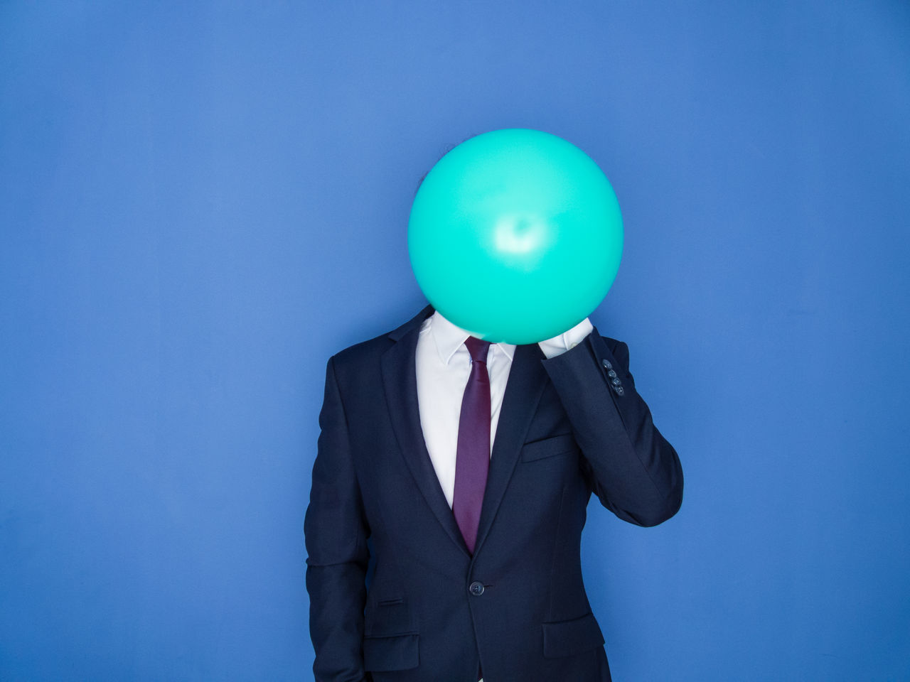 Young handsome bearded man in a suit blowing up a green balloon front view. Blue background. Balloon Beard Blowing Up Balloon Blue Business Business Finance And Industry Businessman Carefree Confidence  Economy Elegant Flower Helium Balloon Holding Man Manager One Person Party Person Relax Self Portrait Suit Well-dressed Young Adult