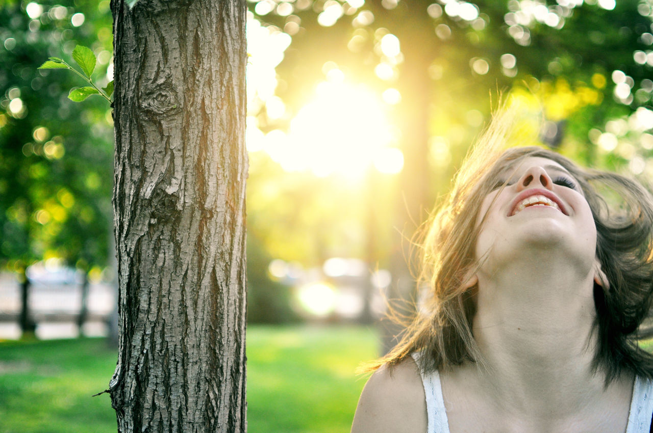 Cheerful Young Woman By Tree At Park On Sunny Day