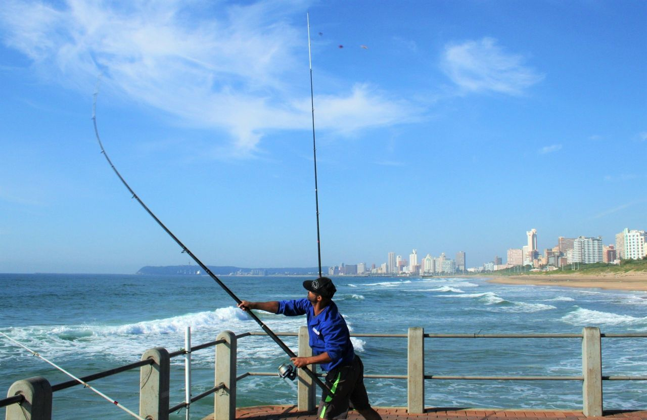 sea, real people, water, railing, one person, leisure activity, fishing, standing, fishing pole, day, holding, sky, horizon over water, outdoors, lifestyles, nature, full length, beauty in nature, architecture, men