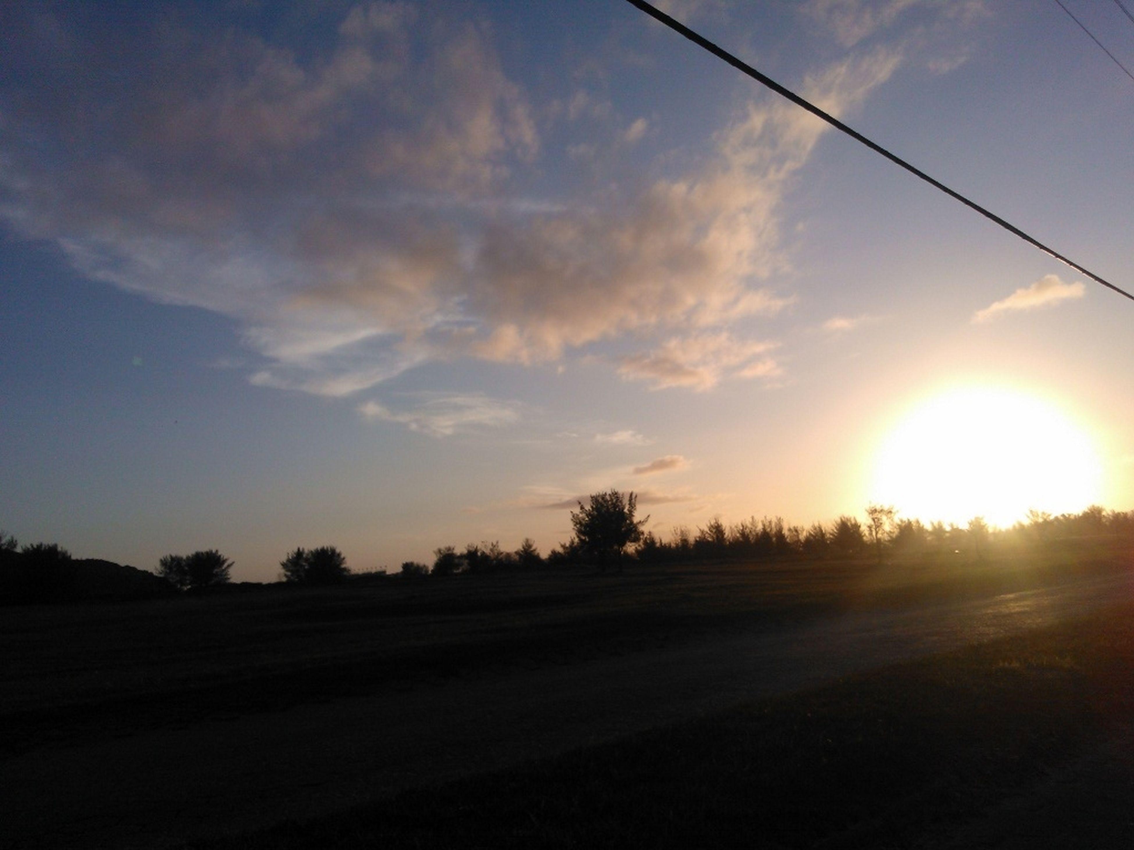 sunset, sun, sky, tranquility, tranquil scene, landscape, silhouette, scenics, beauty in nature, sunlight, nature, sunbeam, orange color, cloud - sky, field, tree, lens flare, idyllic, road, cloud