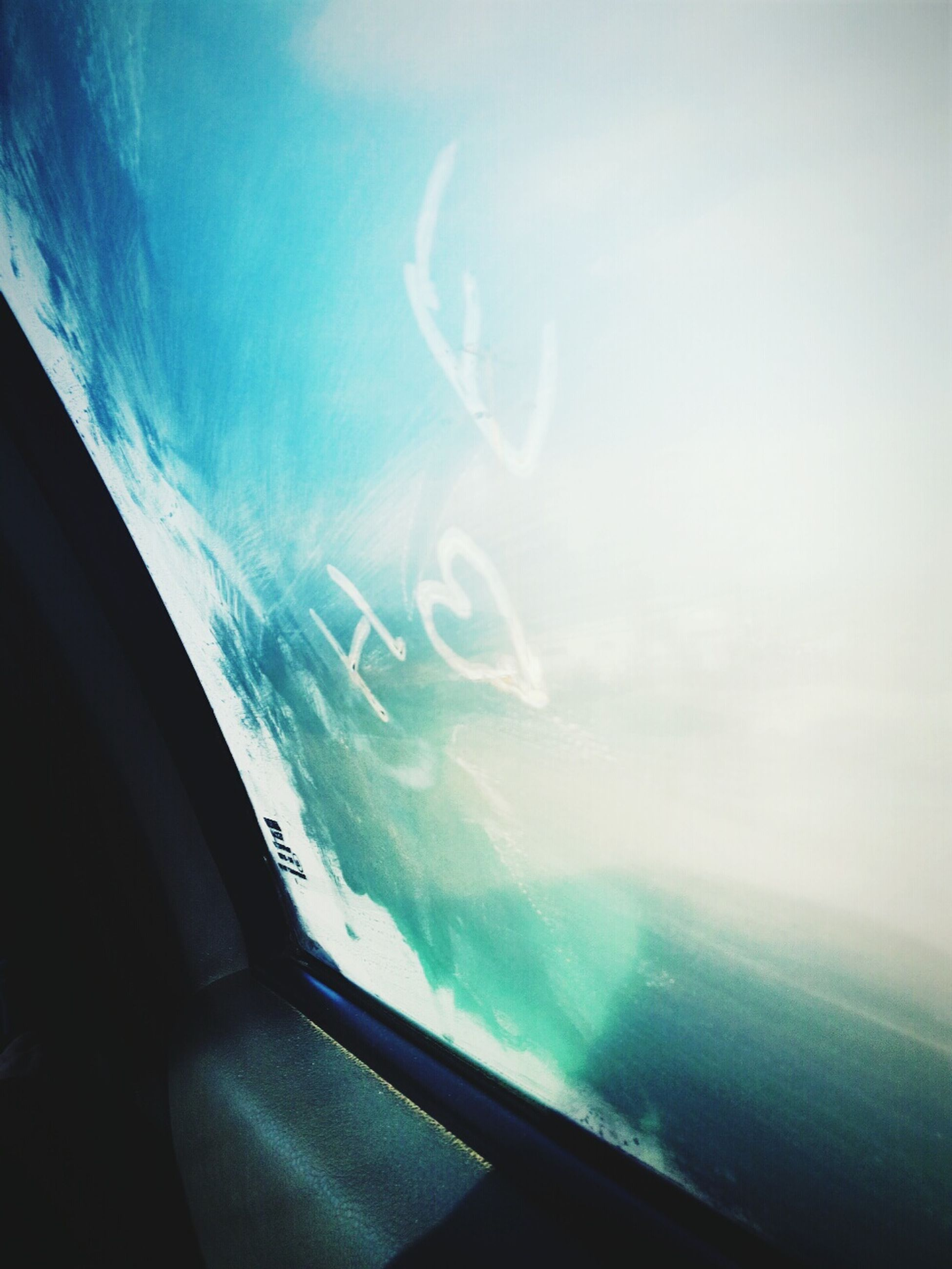 transportation, airplane, vehicle interior, window, mode of transport, glass - material, transparent, air vehicle, sky, blue, part of, aircraft wing, cropped, travel, flying, cloud - sky, windshield, aerial view, on the move, nature