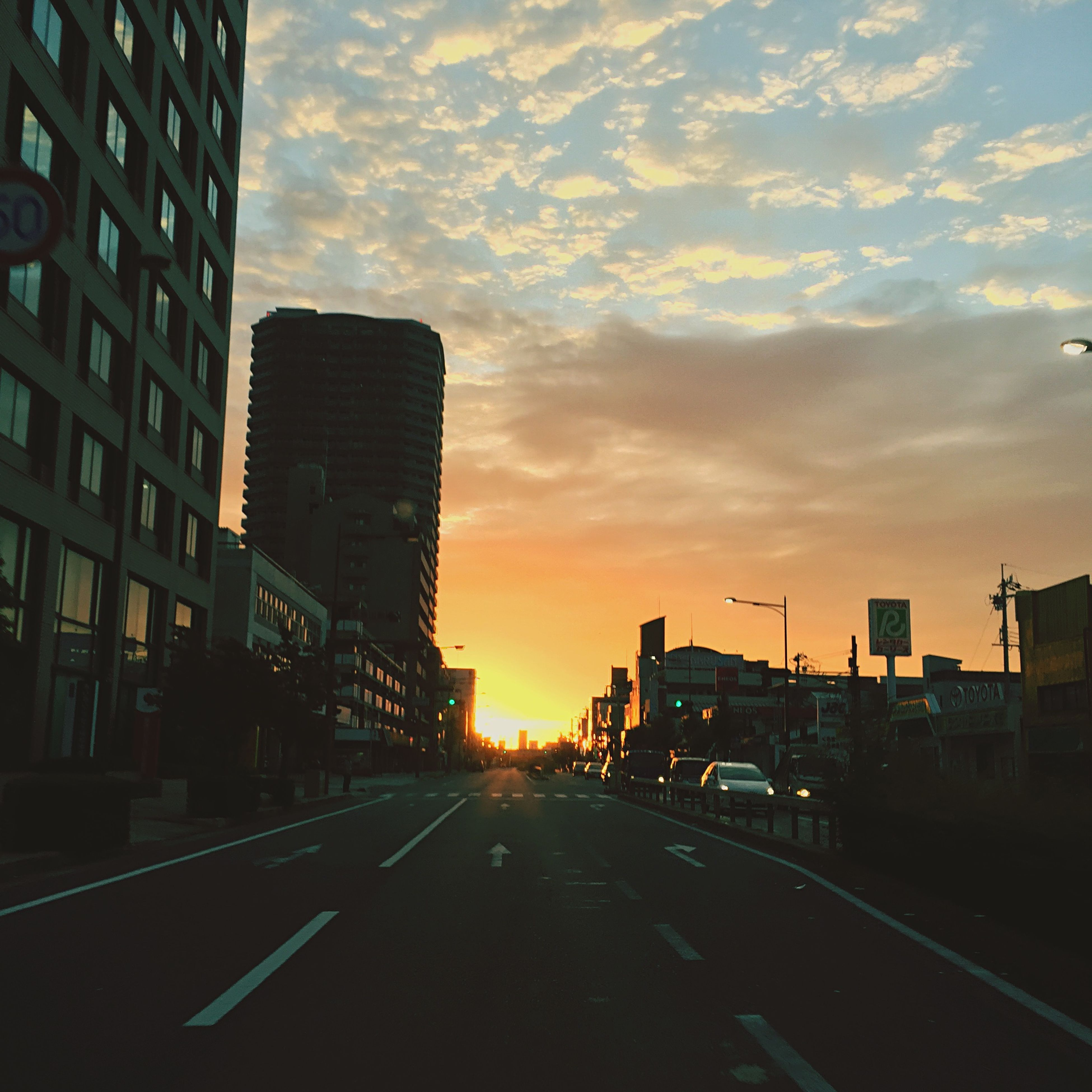 sunset, building exterior, architecture, transportation, built structure, road, the way forward, sky, city, car, street, road marking, diminishing perspective, cloud - sky, land vehicle, orange color, mode of transport, vanishing point, street light, cloud