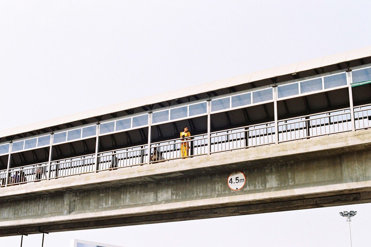 architecture, built structure, clear sky, bridge - man made structure, transportation, low angle view, real people, day, modern, outdoors, men, city, nature, one person, sky, people