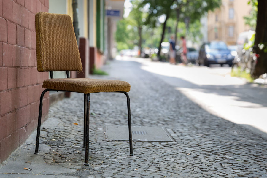 Berlin's abandoned chairs. Last step before disposal of old retro styled chair on cobblestone footpath. Abandoned Aging Process Architecture Bad Condition Brown Built Structure Chair City Cityscape Cobblestone Damaged Day Deterioration Empty Footpath Metal Obsolete Old Outdoors Retirement Retro Styled Seat Single Object The Past Weathered