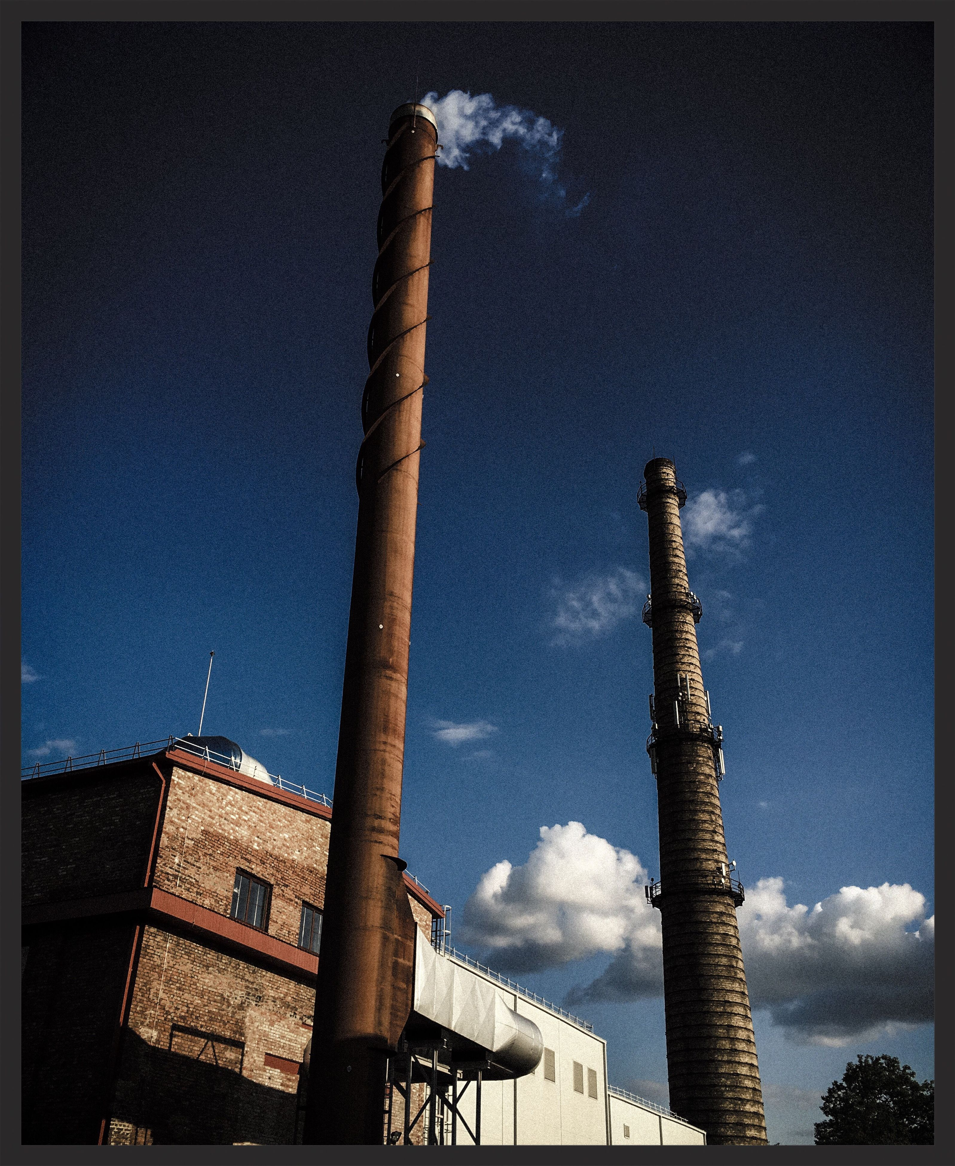 low angle view, built structure, architecture, sky, building exterior, smoke stack, tall - high, auto post production filter, factory, industry, transfer print, cloud - sky, tower, day, no people, outdoors, architectural column, tall, cloud, construction site