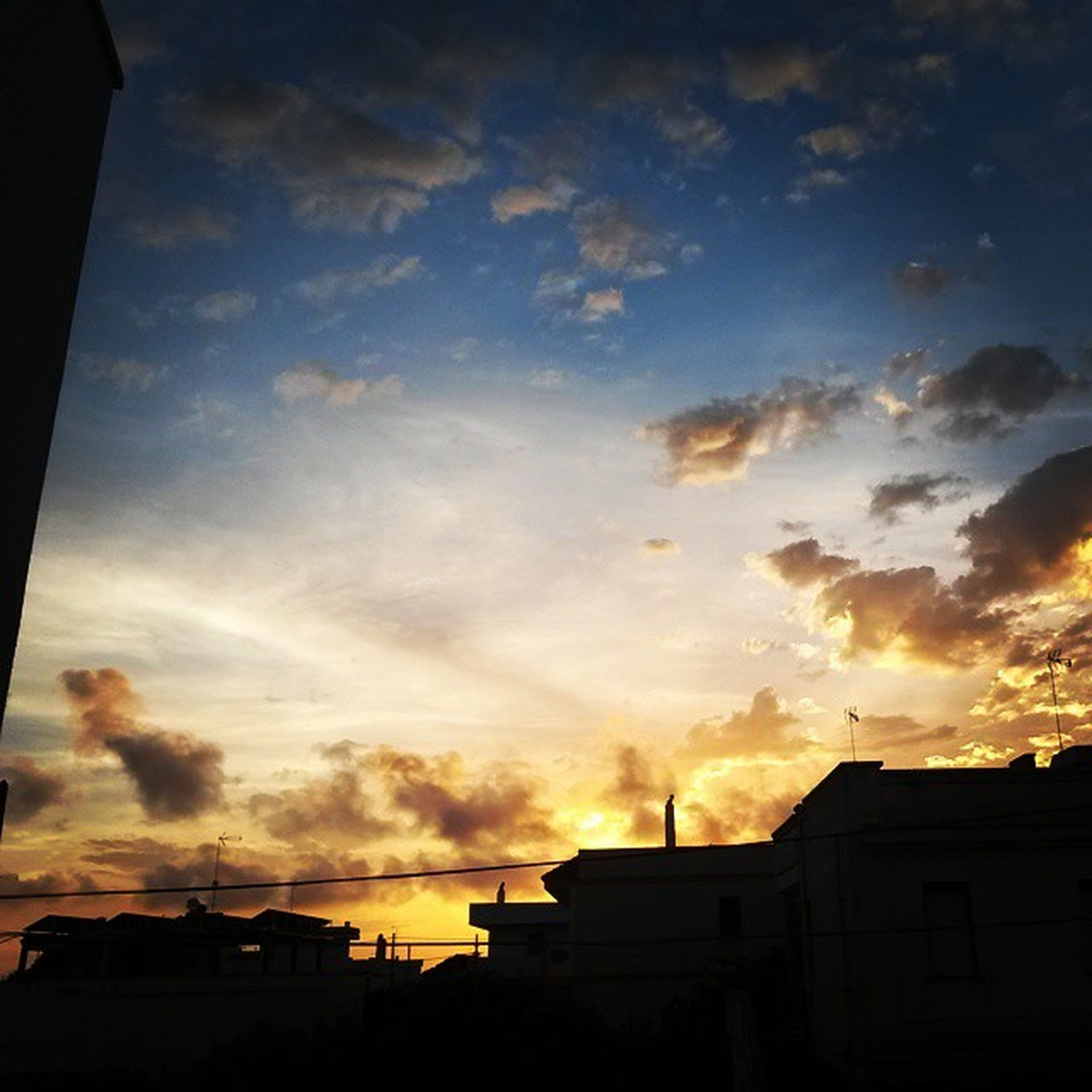 architecture, sunset, building exterior, built structure, sky, low angle view, silhouette, cloud - sky, orange color, house, residential structure, building, residential building, cloud, cloudy, dramatic sky, outdoors, city, nature, no people