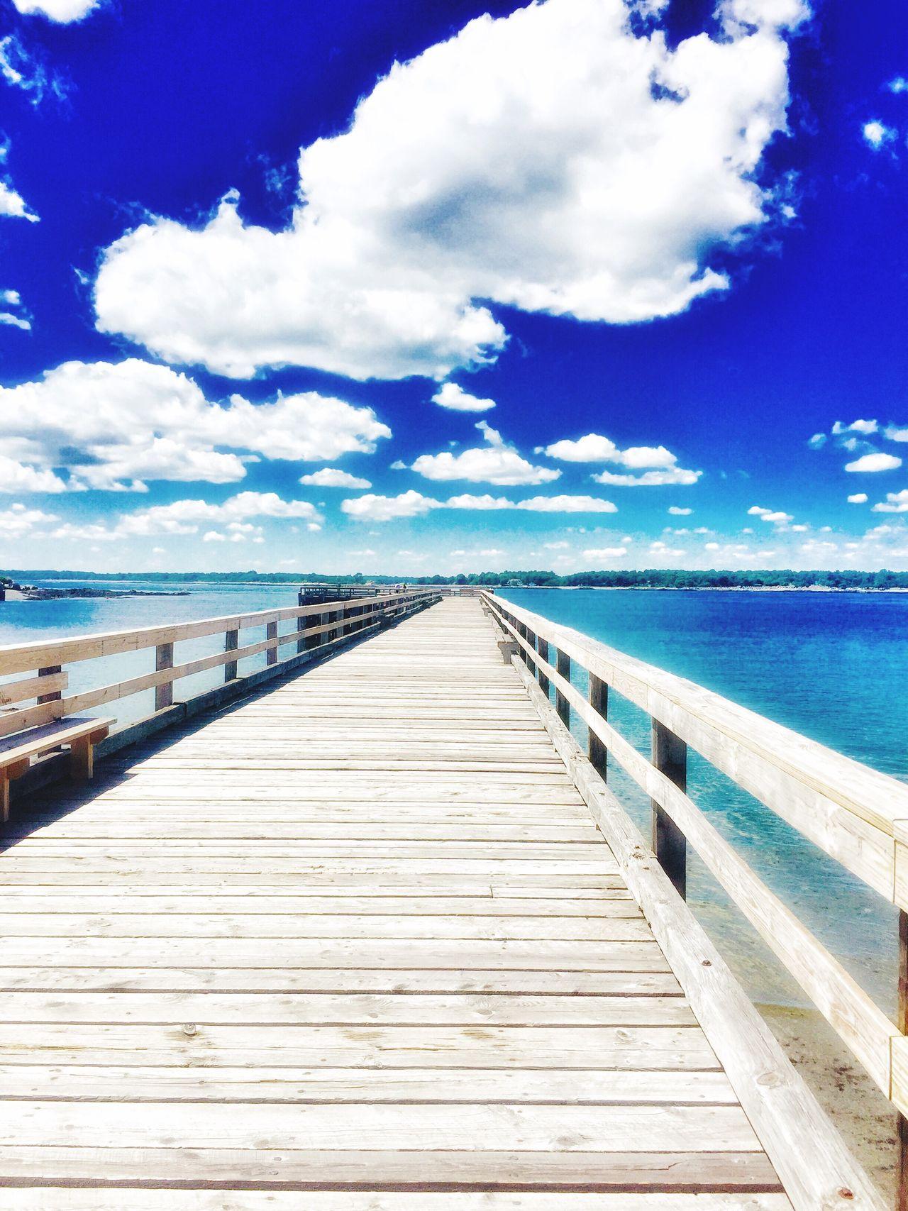 Wooden Pier over the ocean water at fort Foster beach in Kittery, ME Wooden Bridge wooden pier, daylight, sunlight, White Clouds Wooden Pier Sunlight ☀ Daylight Bright Blue Sky East Coast