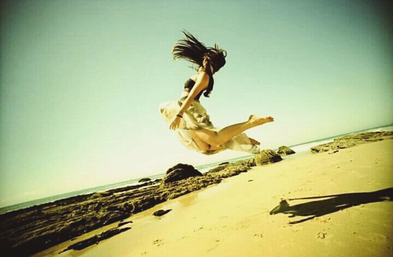 jumping, mid-air, motion, full length, beach, activity, dancing, sand, one person, adult, adults only, one woman only, flying, young adult, wind, only women, sea, people, outdoors, one young woman only, women, human body part, day, young women, energetic, sky